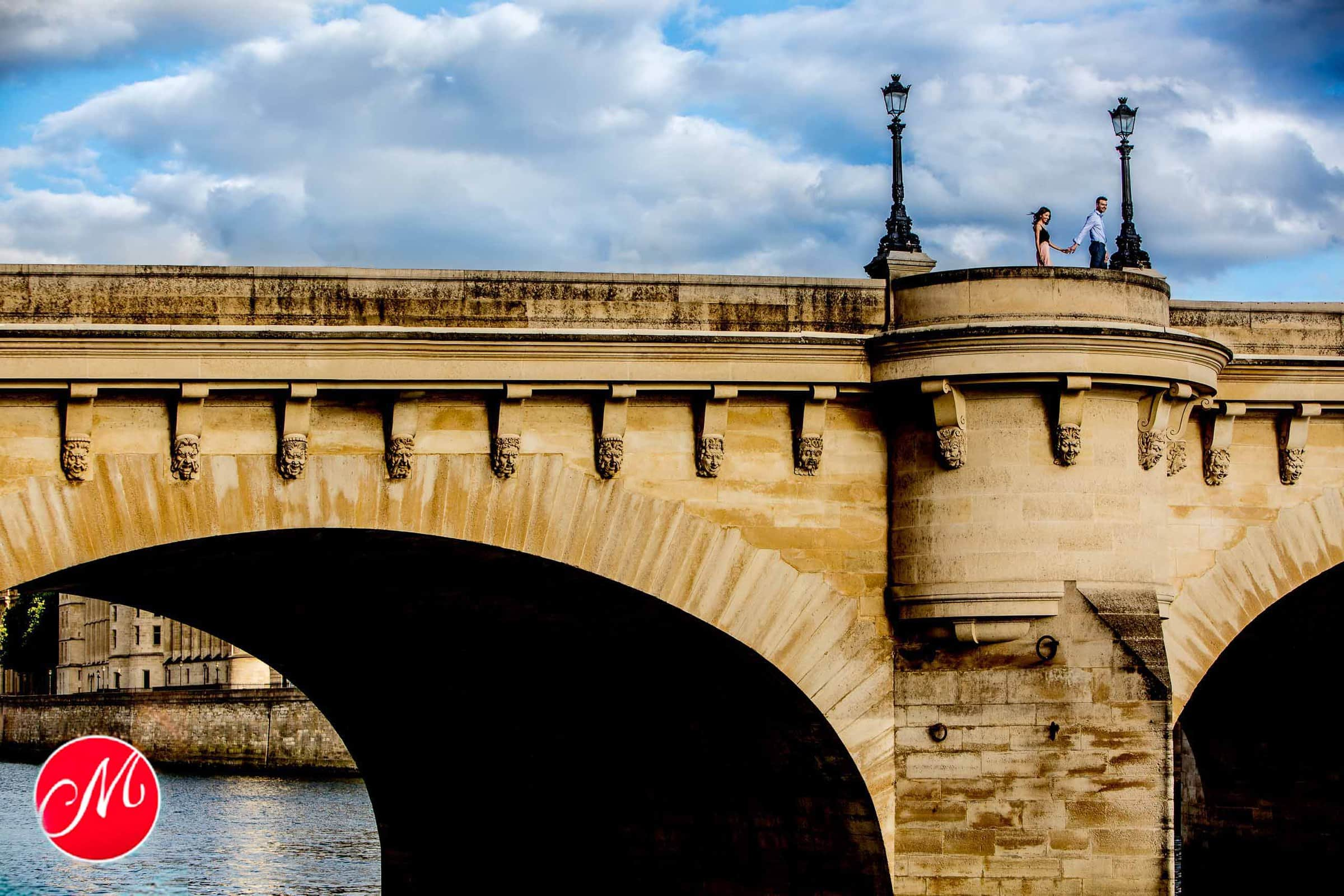 Engagement photo in Paris with a couple walking over the Pont Neuf bridge. This was definitely one of our best of 2019