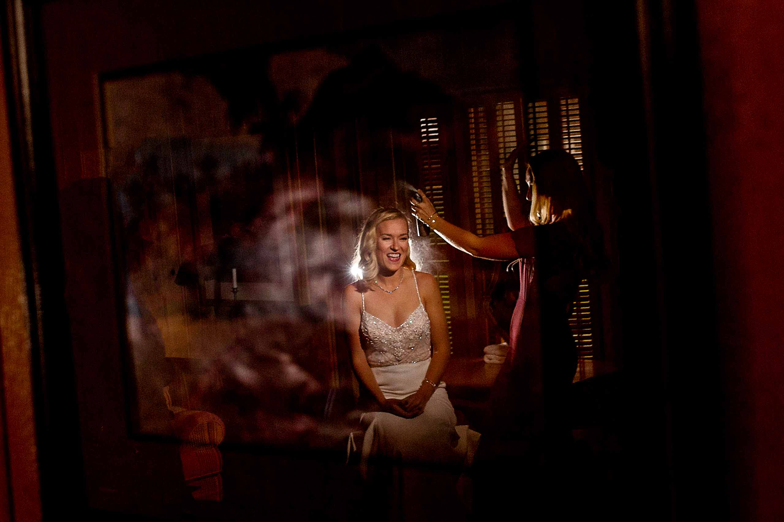 Bride getting ready with hair spray before her House on Metolius wedding ceremony