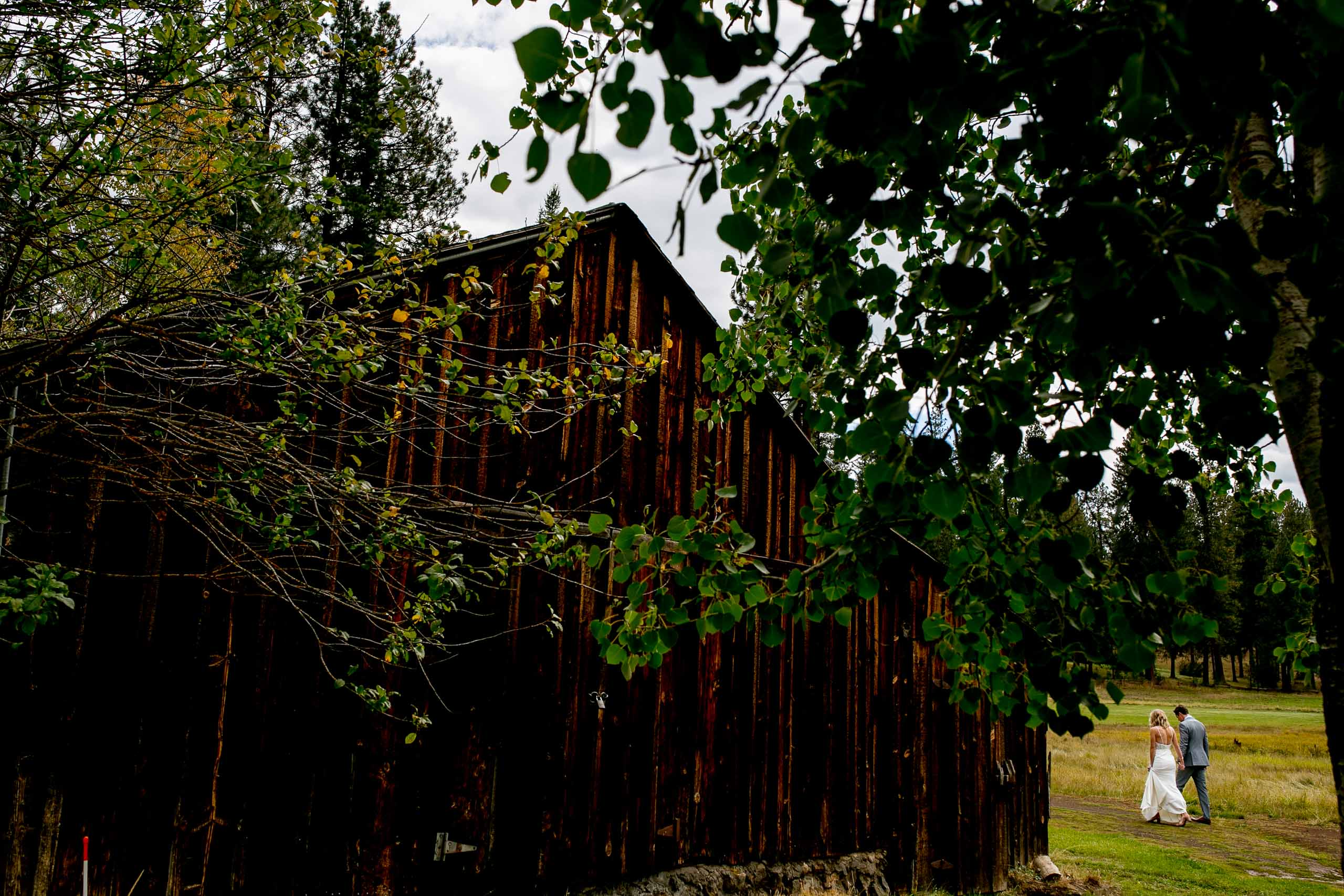 Bride and groom walking near a barn before their House on Metolius wedding