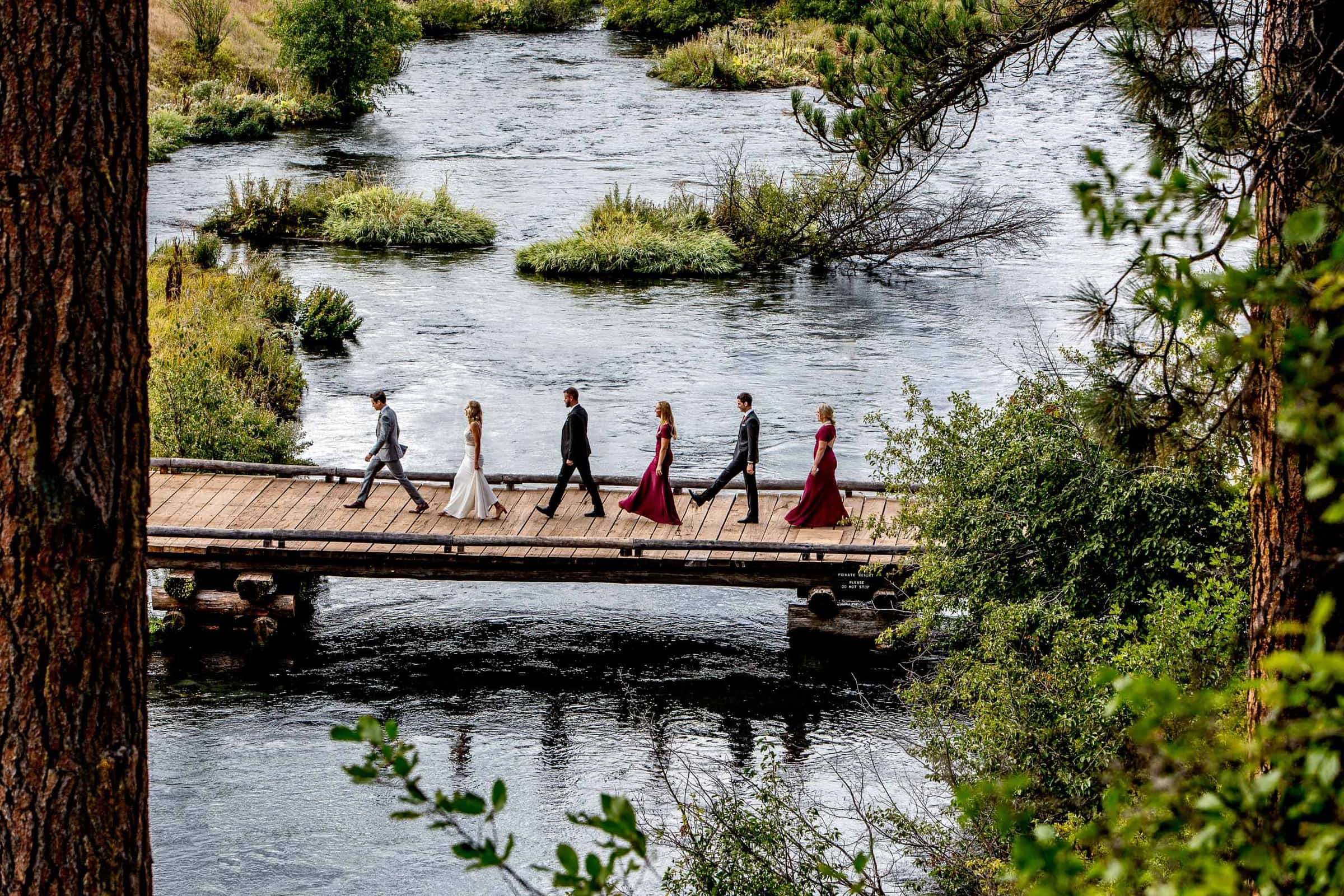 Bridal party walking across a bridge before a House on Metolius wedding