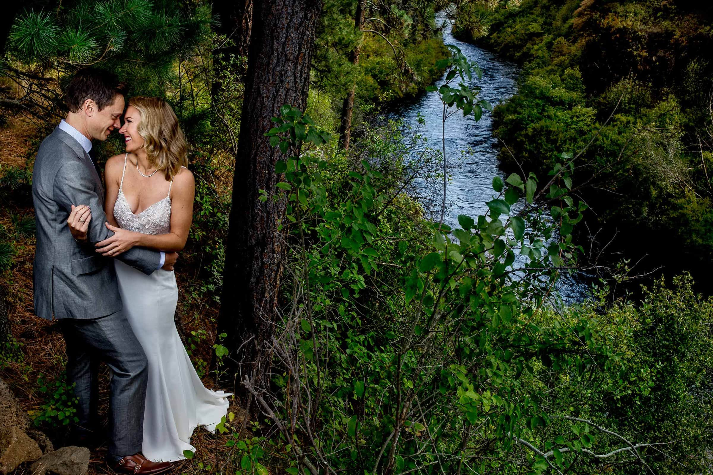 Gorgeous portrait of bride and groom near a zigzag river during their House on Metolius Wedding celebration