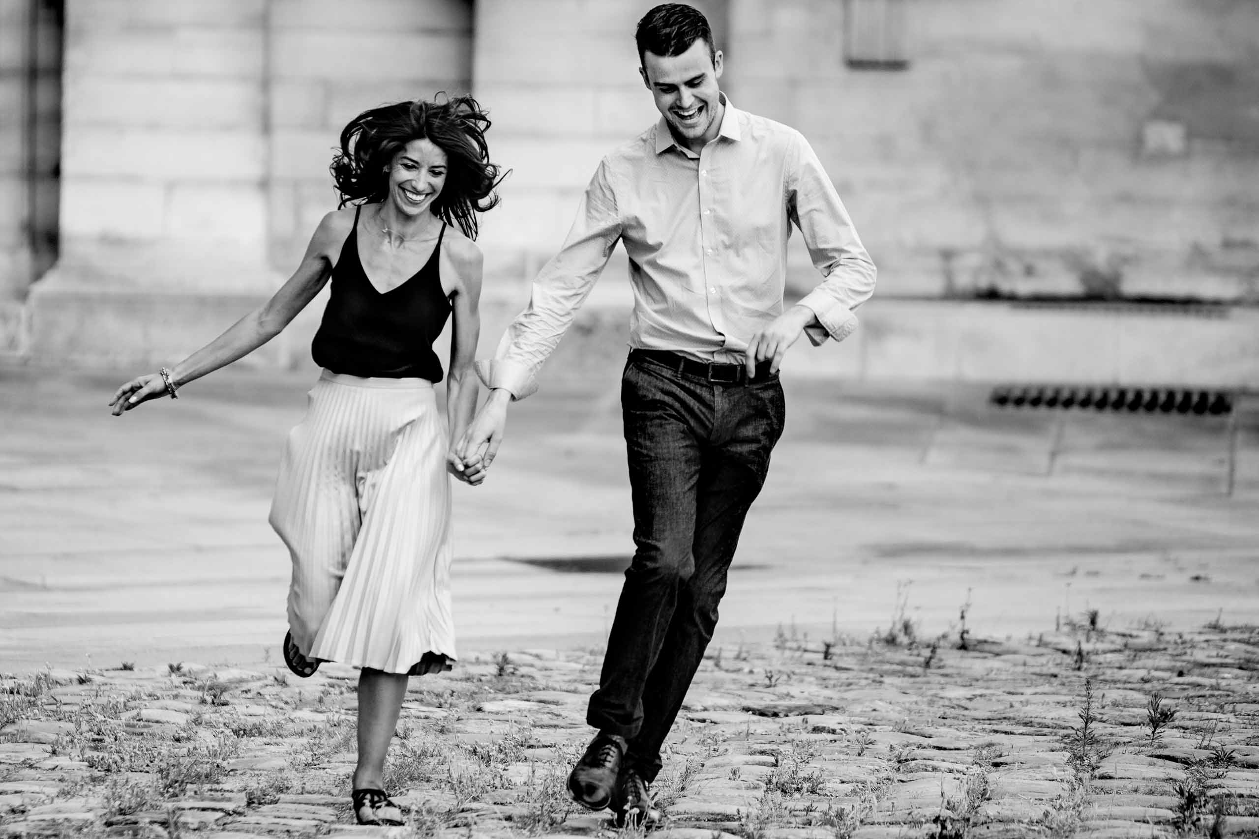 A creative portrait of a couple running toward the Louvre during their Paris engagement photo session