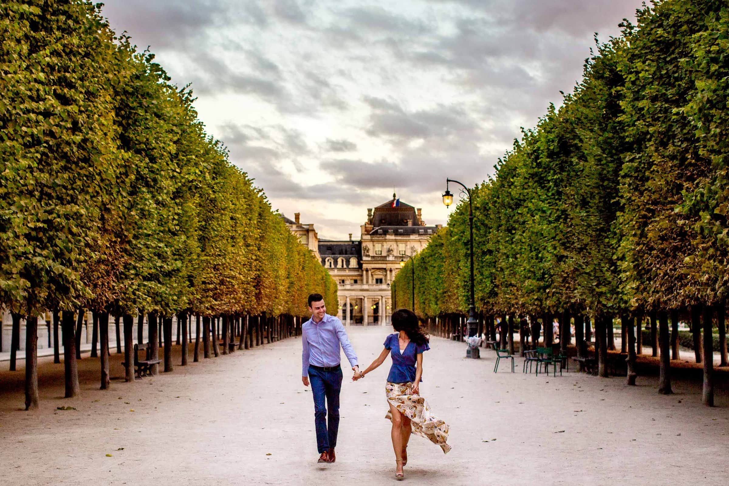 A creative portrait of a couple walking hand and hand in a garden during their Paris engagement photo session