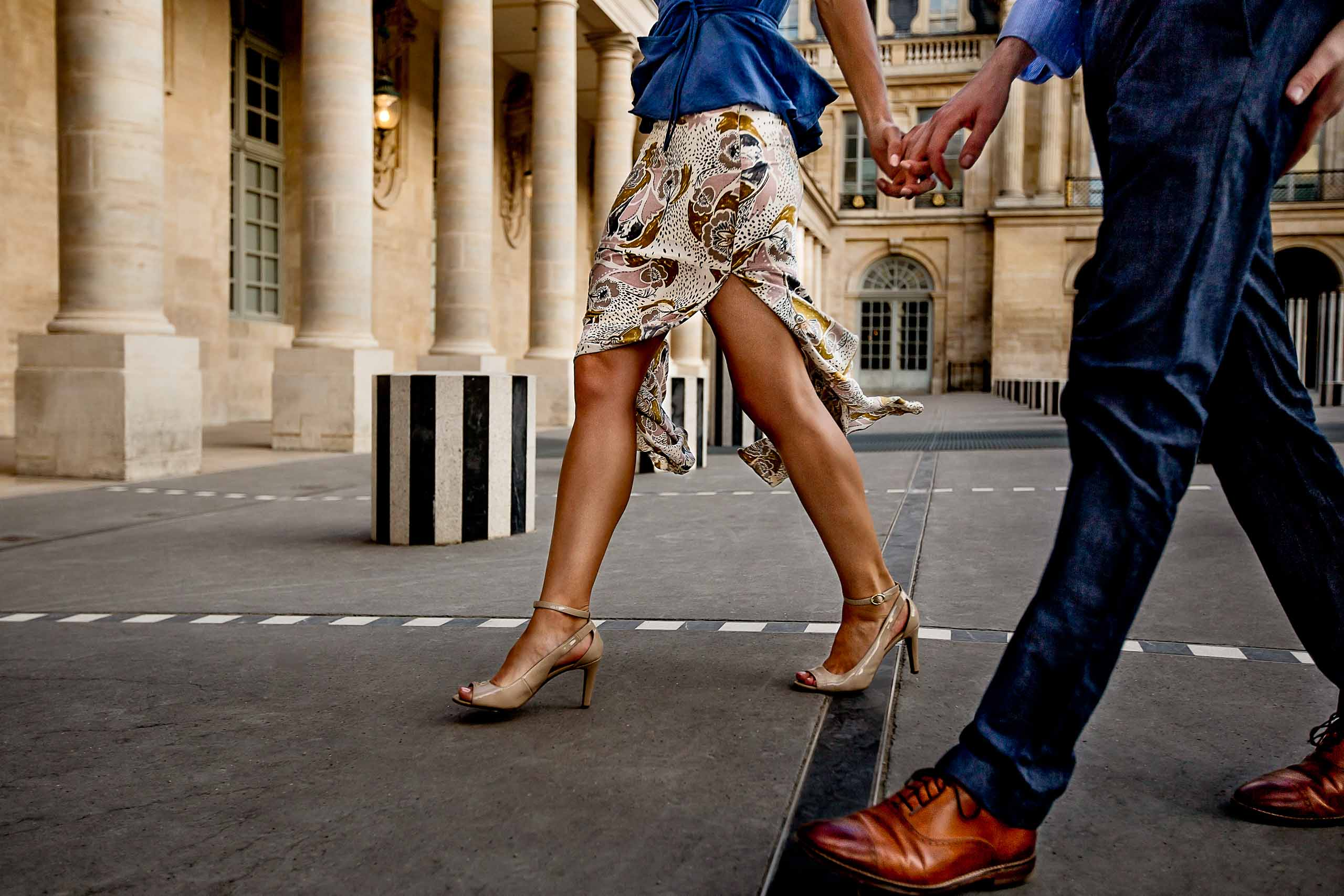 A creative portrait of a couple walking hand and hand during their Paris engagement photo session