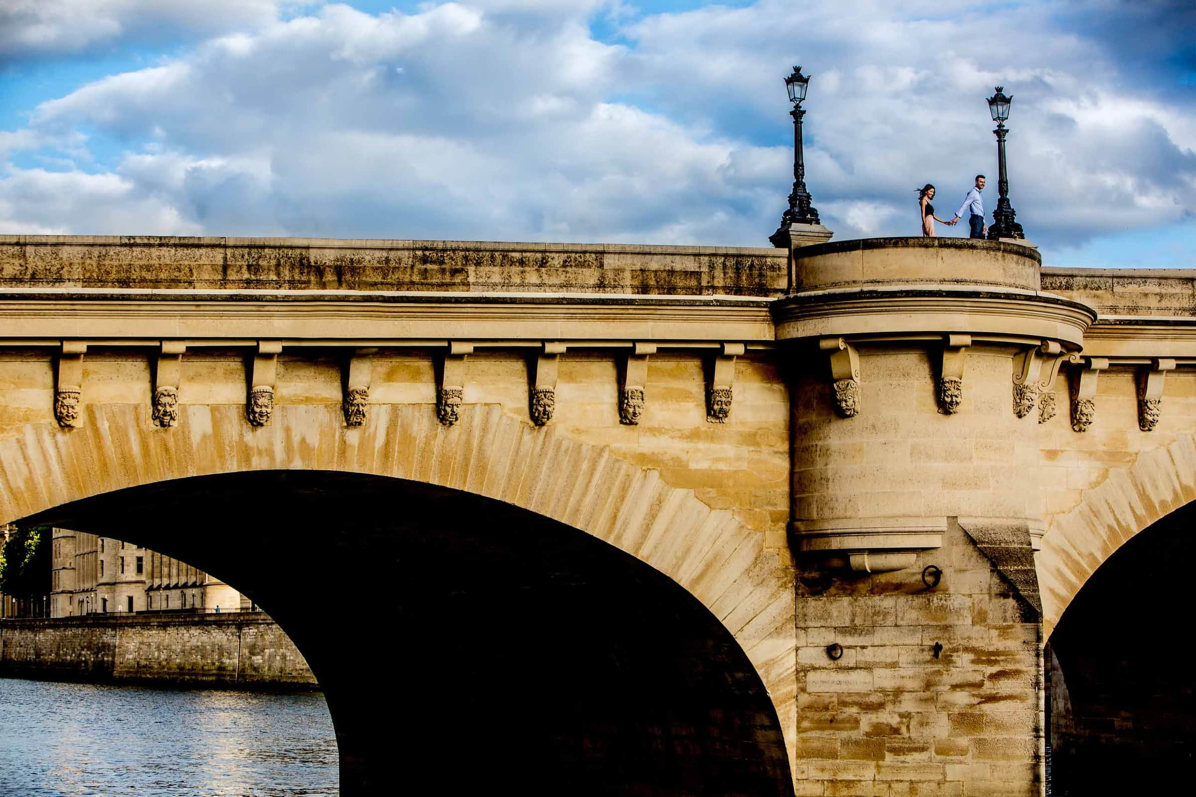 Stunning Paris Engagement photos of a couple walking hand and hand on Pont Neuf.