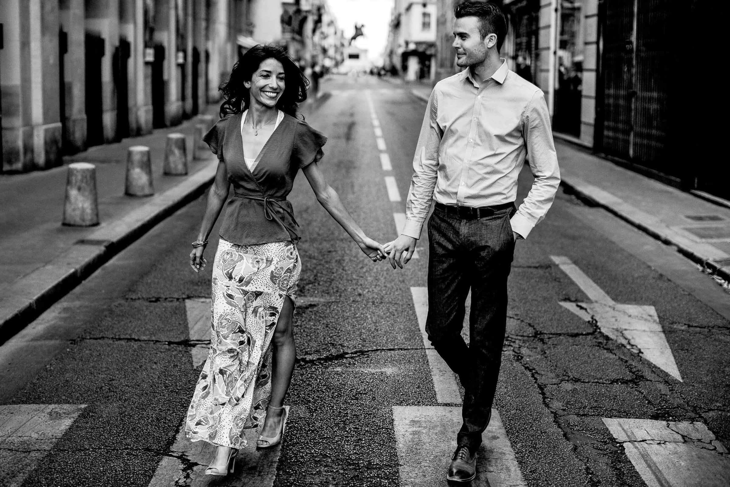 A creative portrait of a couple walking hand and hand in the back streets during their Paris engagement photo session