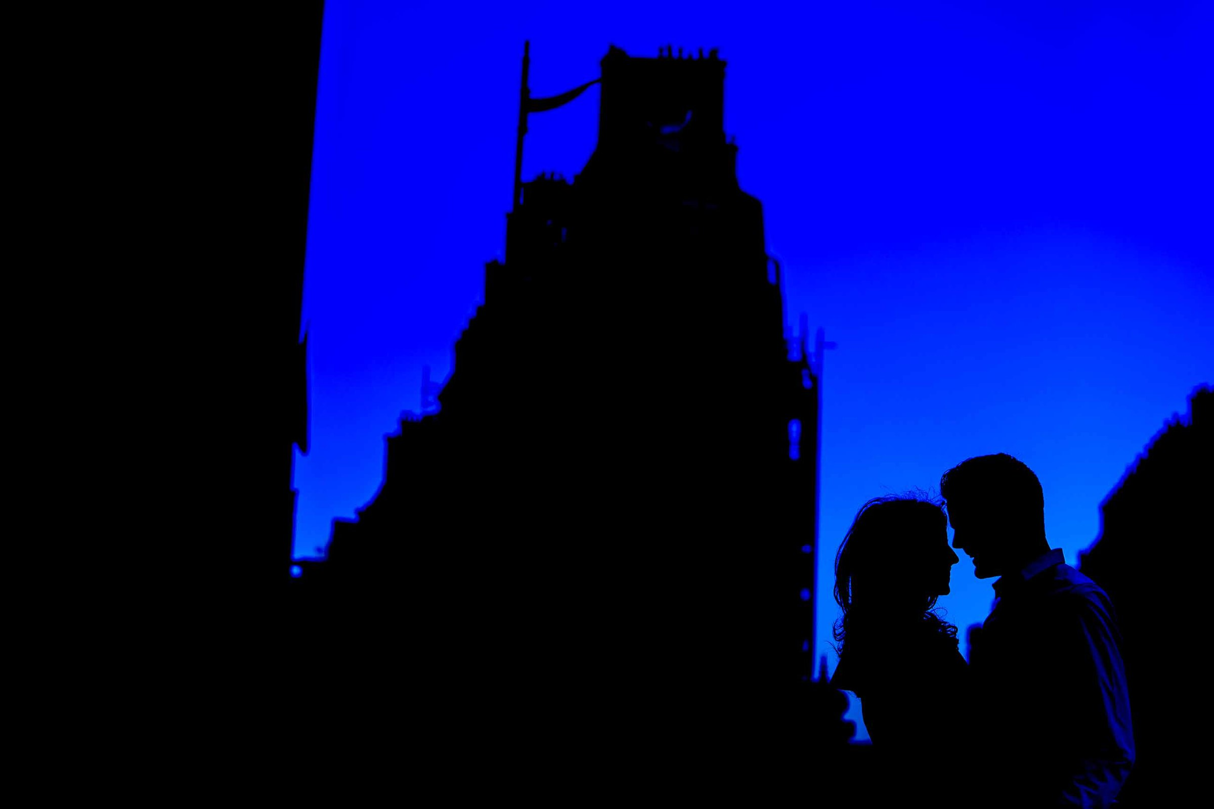 A creative portrait of a couple embracing in a silhouette during their Paris engagement photo session