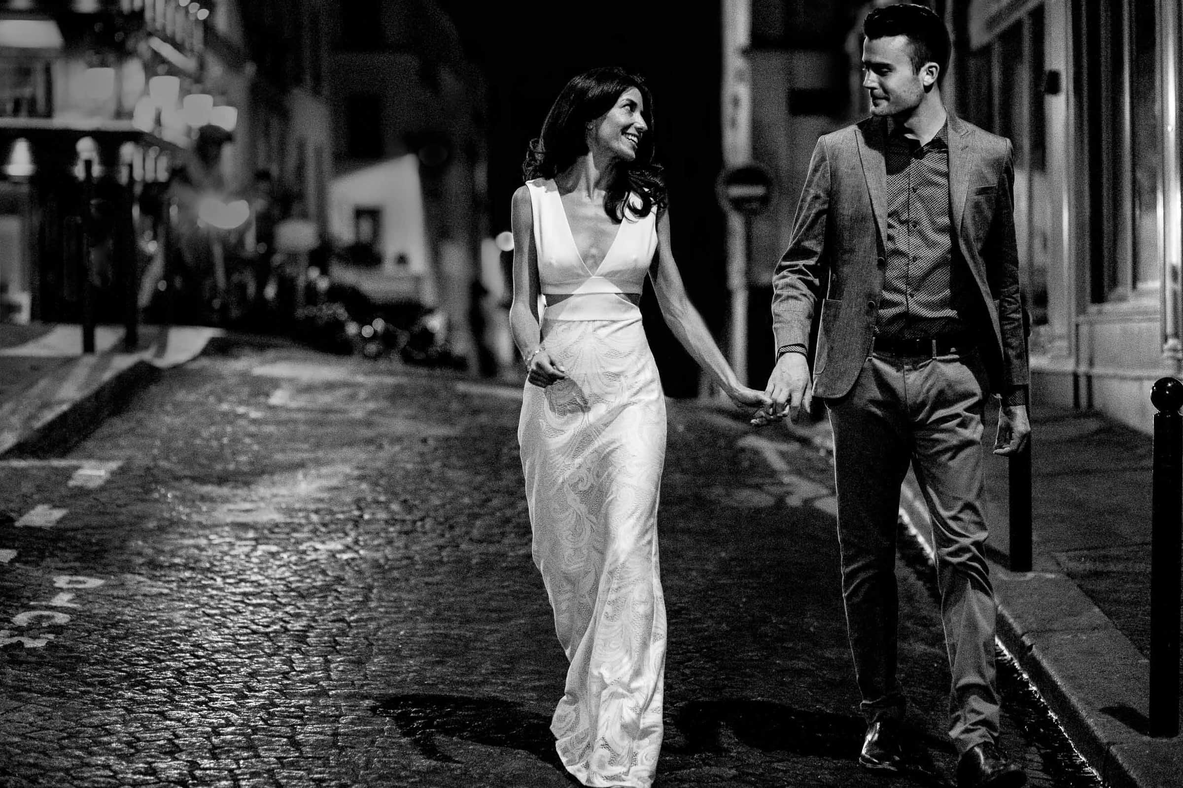 A creative portrait of a couple walking hand and hand in back streets during their Paris engagement photo session