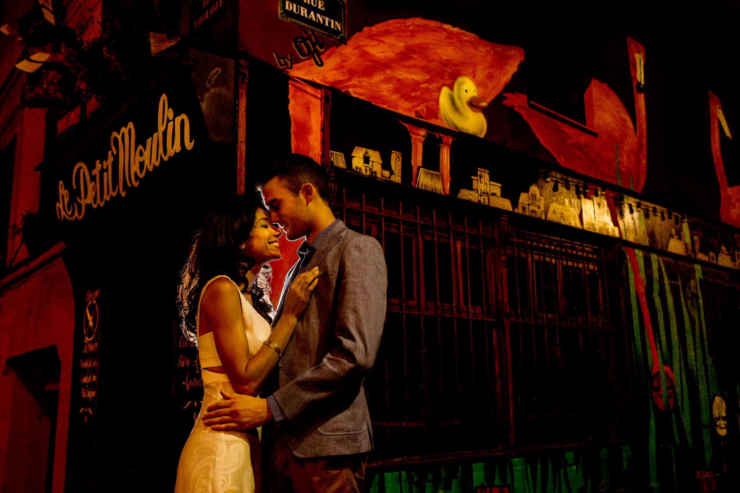 A creative portrait of a couple embracing near de Petit Moulin during their Paris engagement photo session