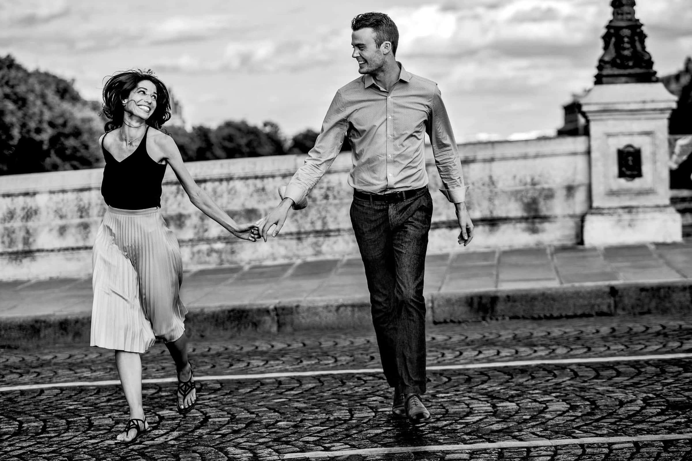 A creative portrait of a couple walking hand and hand on Pont Neuf during their Paris engagement photo session
