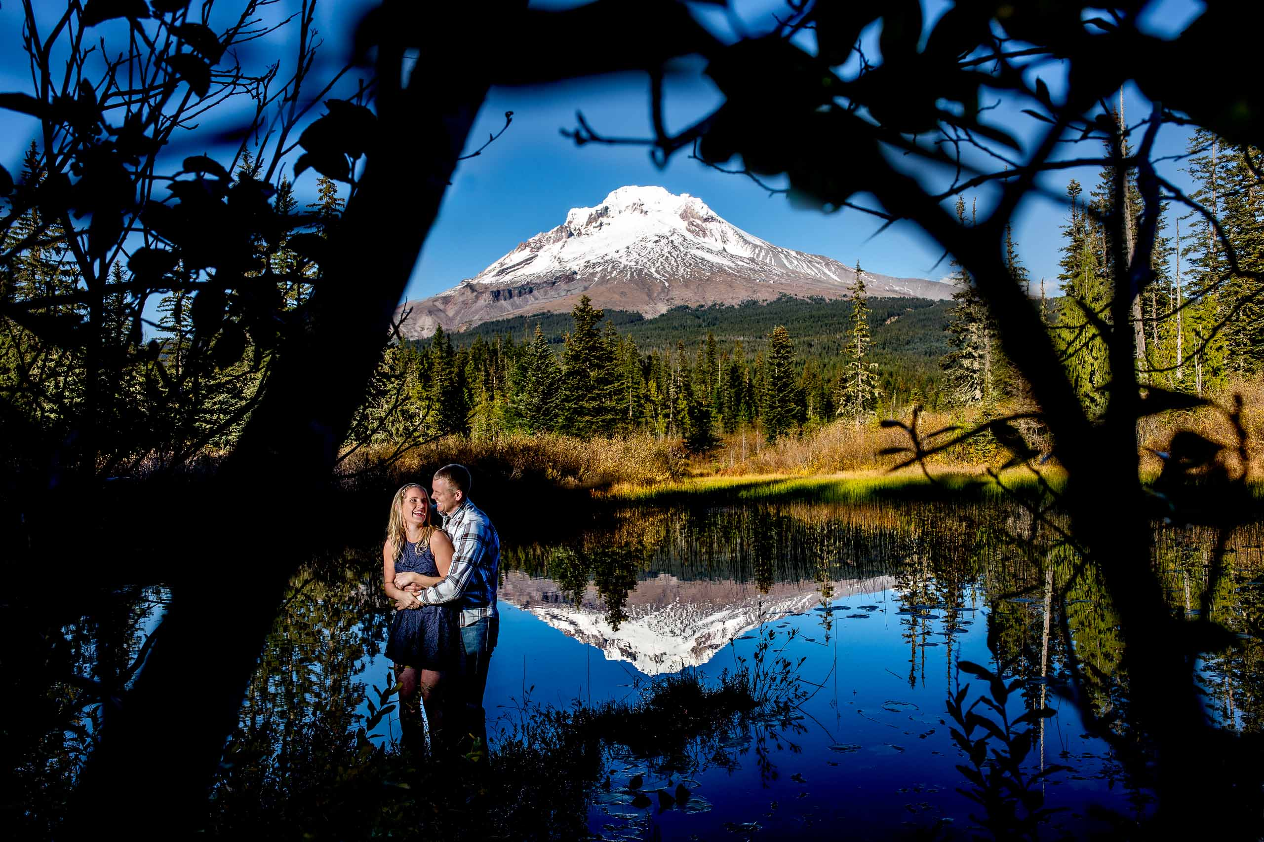 A fantastic photo of a couple in a hidden lake with Mt Hood reflection for their Mt Hood engagement photos