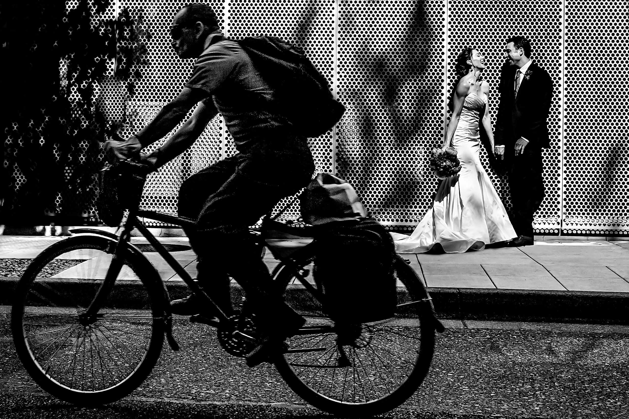 Portland biker riding by infront of bride and groom laughing in Portland Oregon just outside Eco Trust Building in the Pearl district.