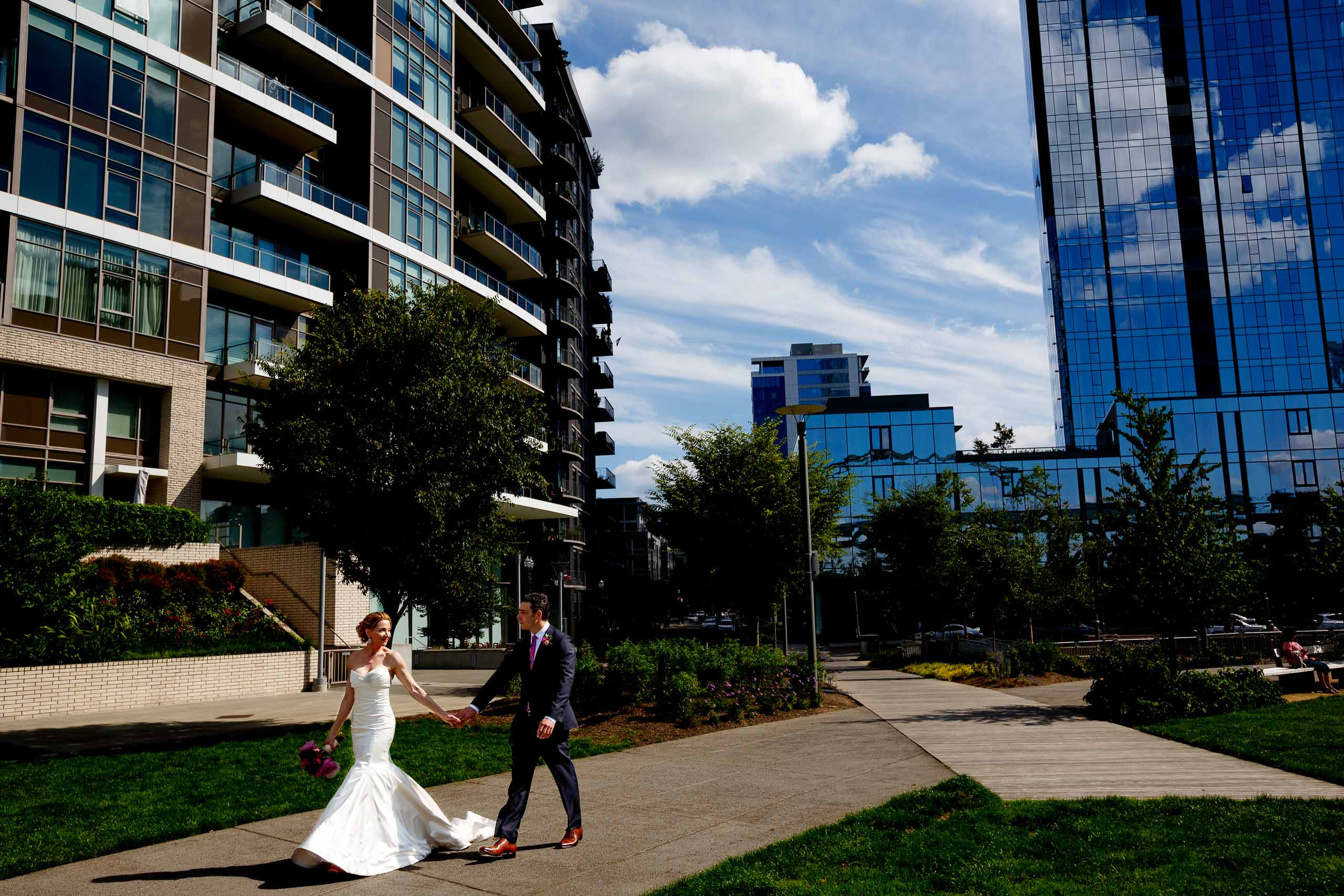 Wide angle perspective of bride and groom walking toward their EcoTrust wedding in Portland, Oregon
