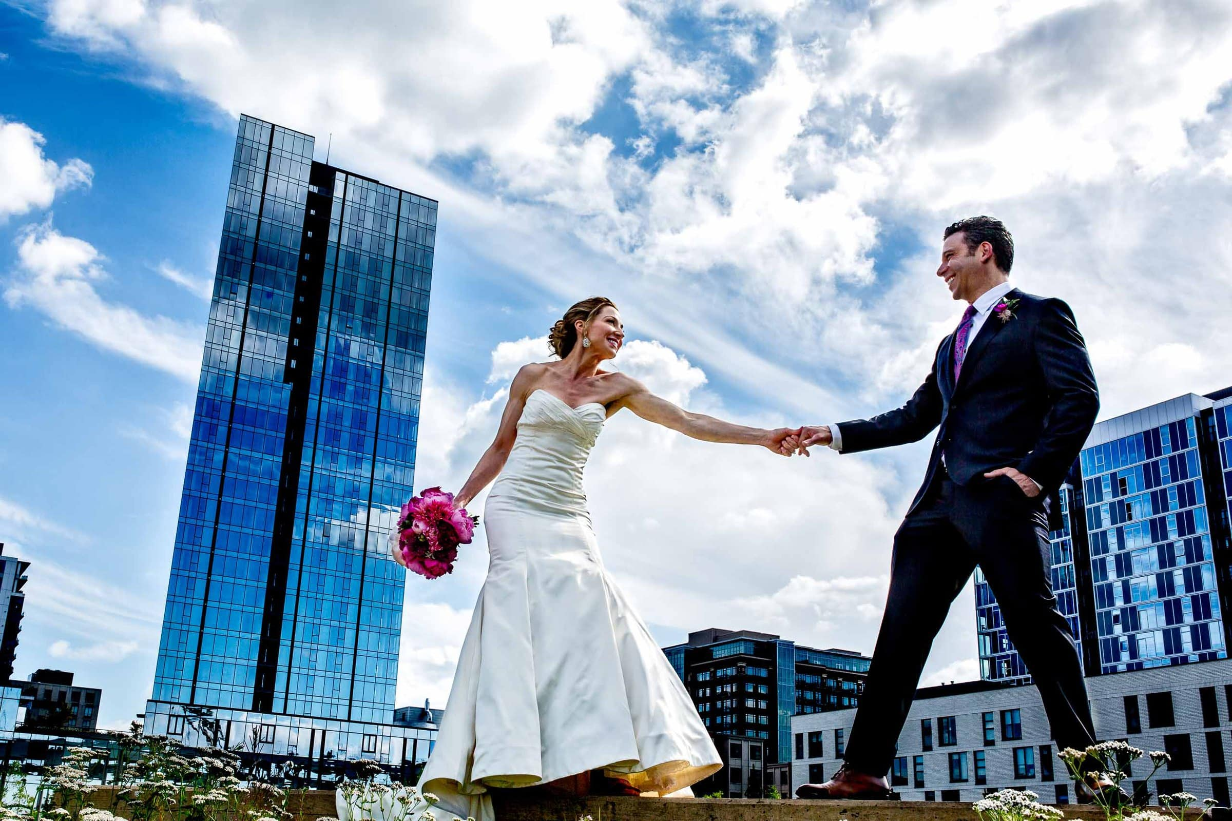Wide angle perspective of bride and groom dancing in the city before their EcoTrust wedding in Portland, Oregon