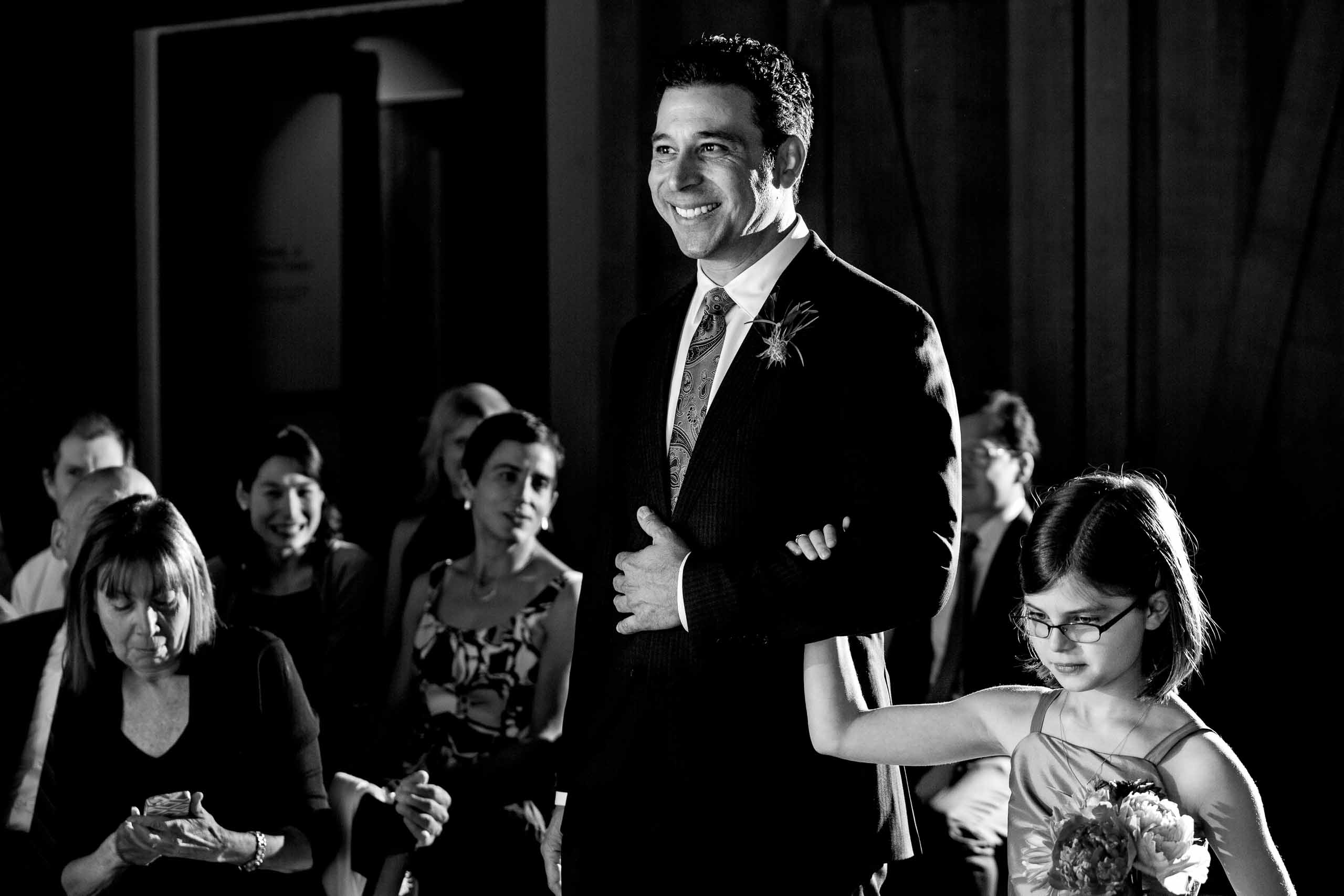 Groom walking into an EcoTrust wedding ceremony with his daughter.