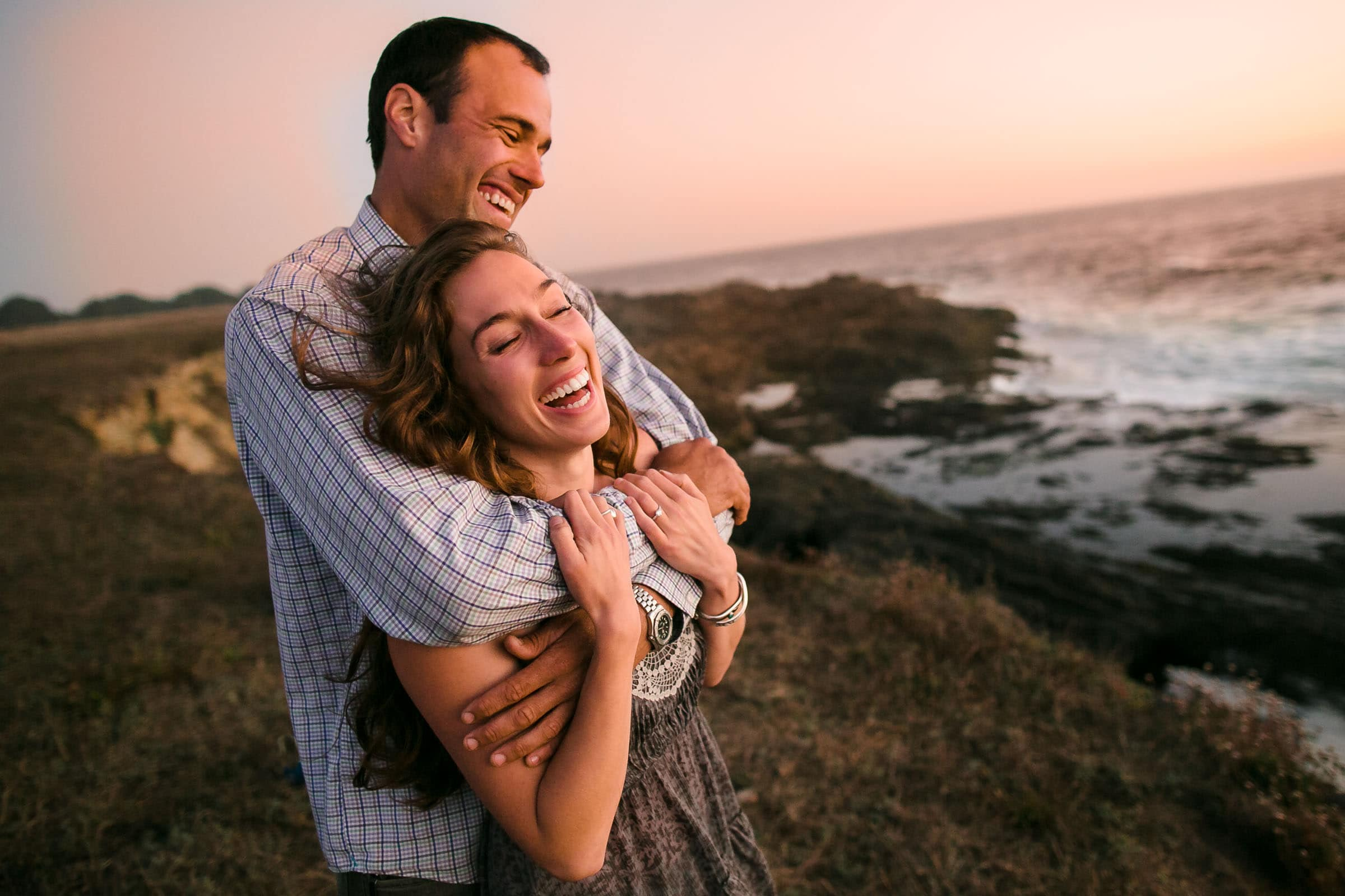 Engagement photo of a couple on cliffs looking out over the ocean the night before their Mendocino Coast wedding at Spring Ranch