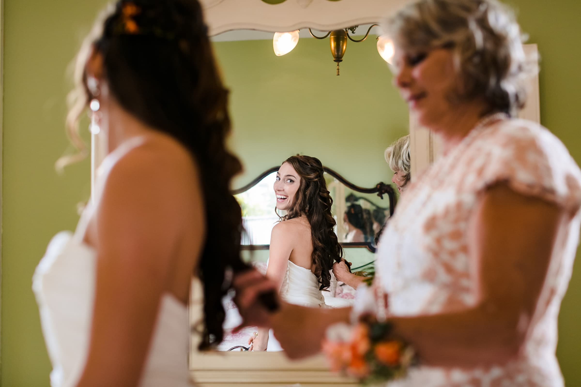 A story telling photo of a bride getting her hair done for her Mendocino Coast wedding at Spring Ranch