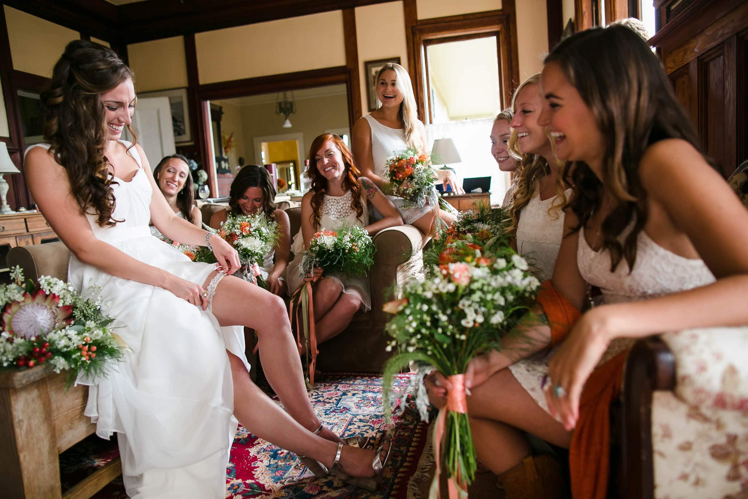 Happy bride getting ready while putting on her garter with friends surrounding her for her Mendocino Coast wedding at Spring Ranch