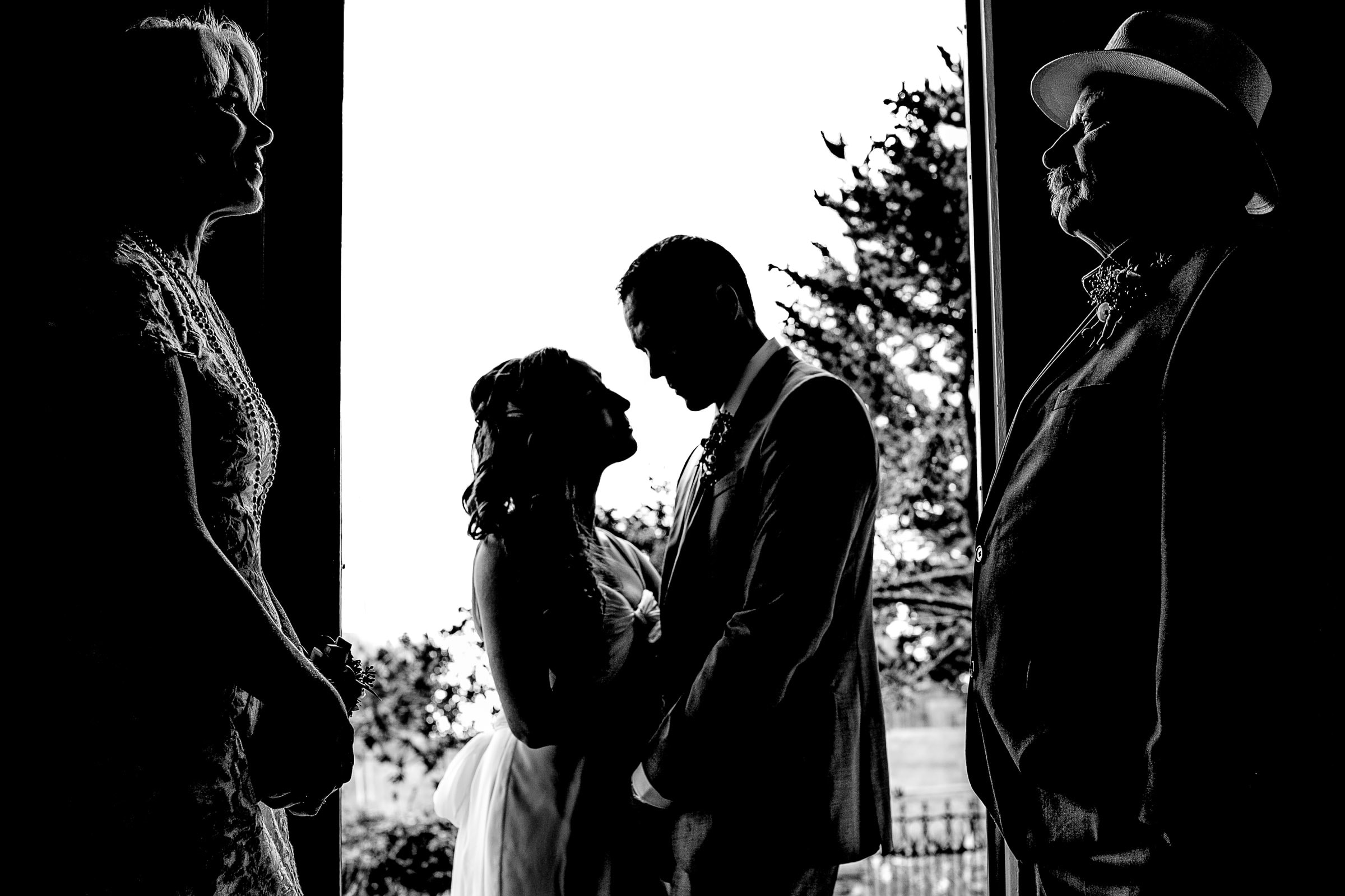 A beautiful photo of a bride and groom silhouetted with parents faces in a doorway just moments before their Mendocino Coast wedding at Spring Ranch