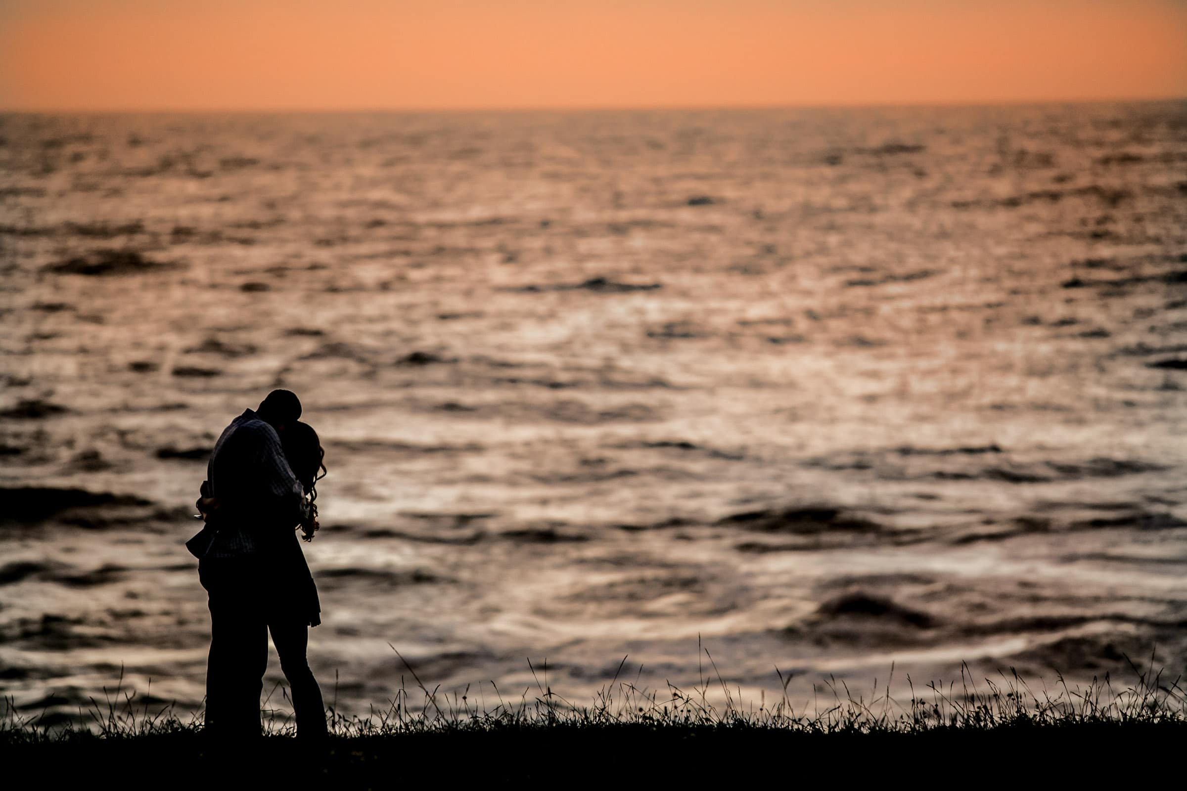 Silhouette of a couple holding each other while looking out over the ocean and warm sunset the night before their Mendocino Coast wedding at Spring Ranch