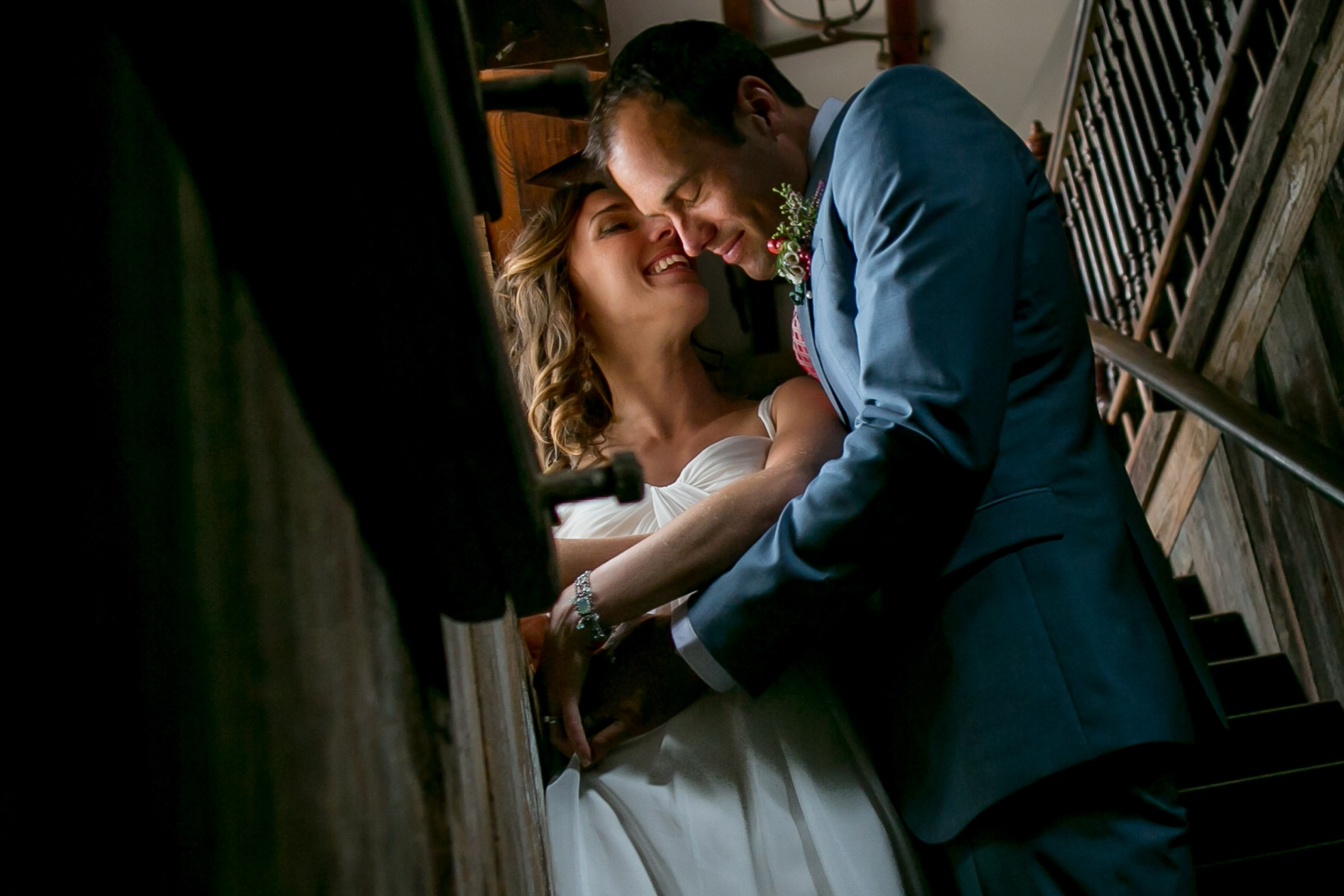 A bride and groom embracing in a barn near a window during their Mendocino Coast wedding at Spring Ranch