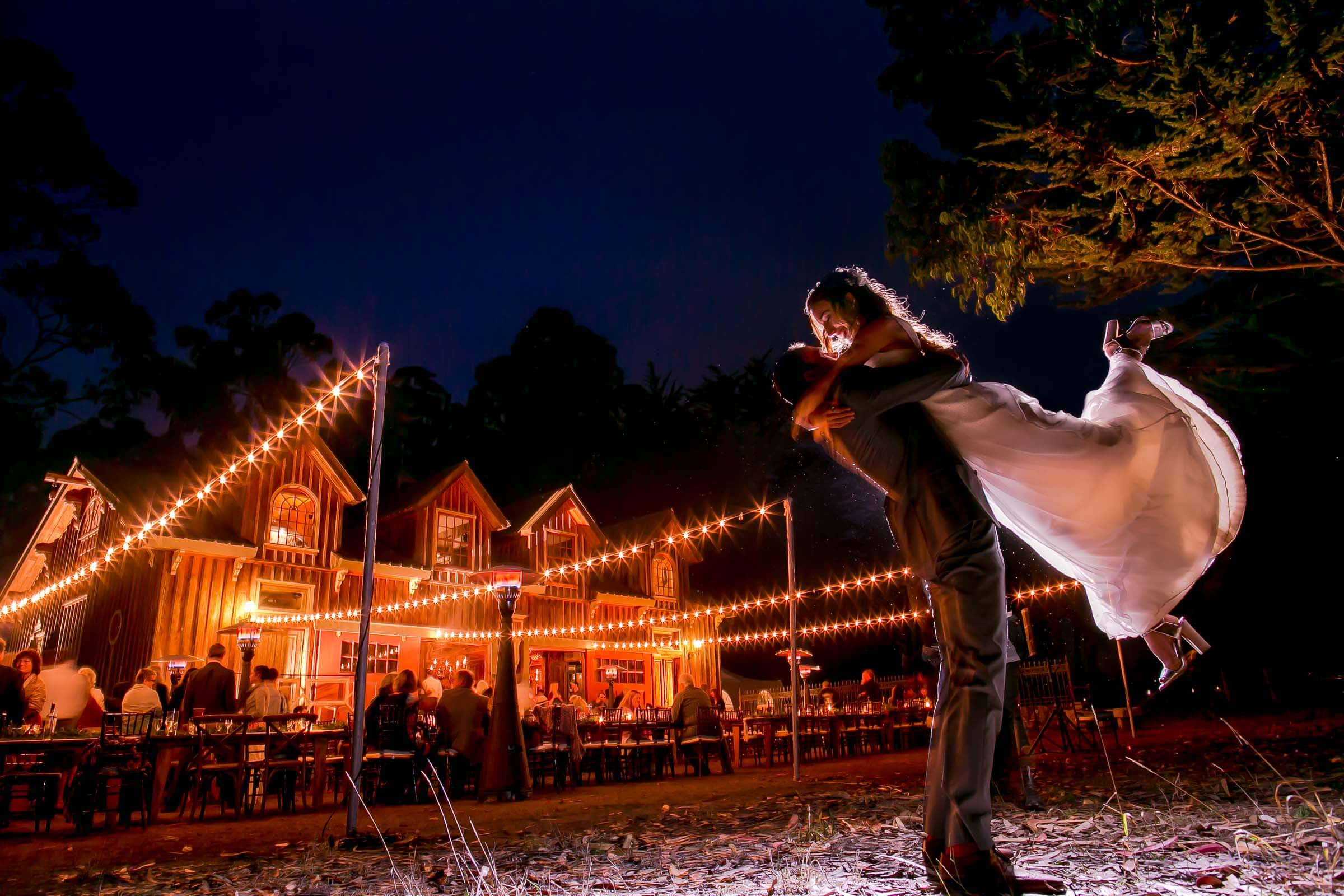 A bride and groom hugging and flying up in the air together during their Mendocino Coast wedding reception at Spring Ranch