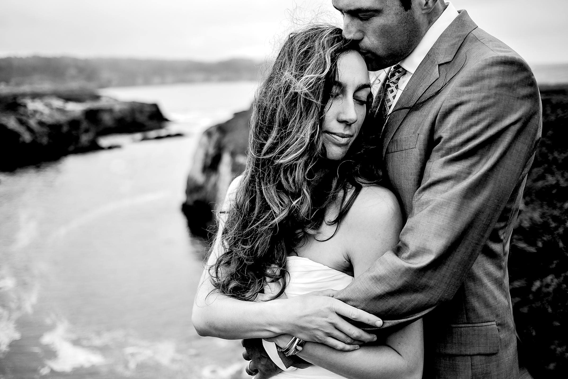A beautiful black and white photo of a couple authentically embracing each other on bluffs near the Pacific ocean the day after their Mendocino Coast wedding at Spring Ranch