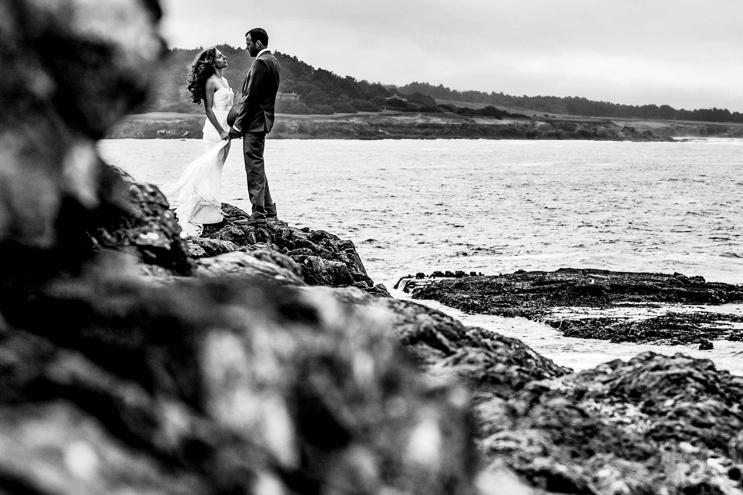 A black and white photo of bride and groom on the cliffs together near the Pacific ocean the day after their Mendocino Coast wedding at Spring Ranch