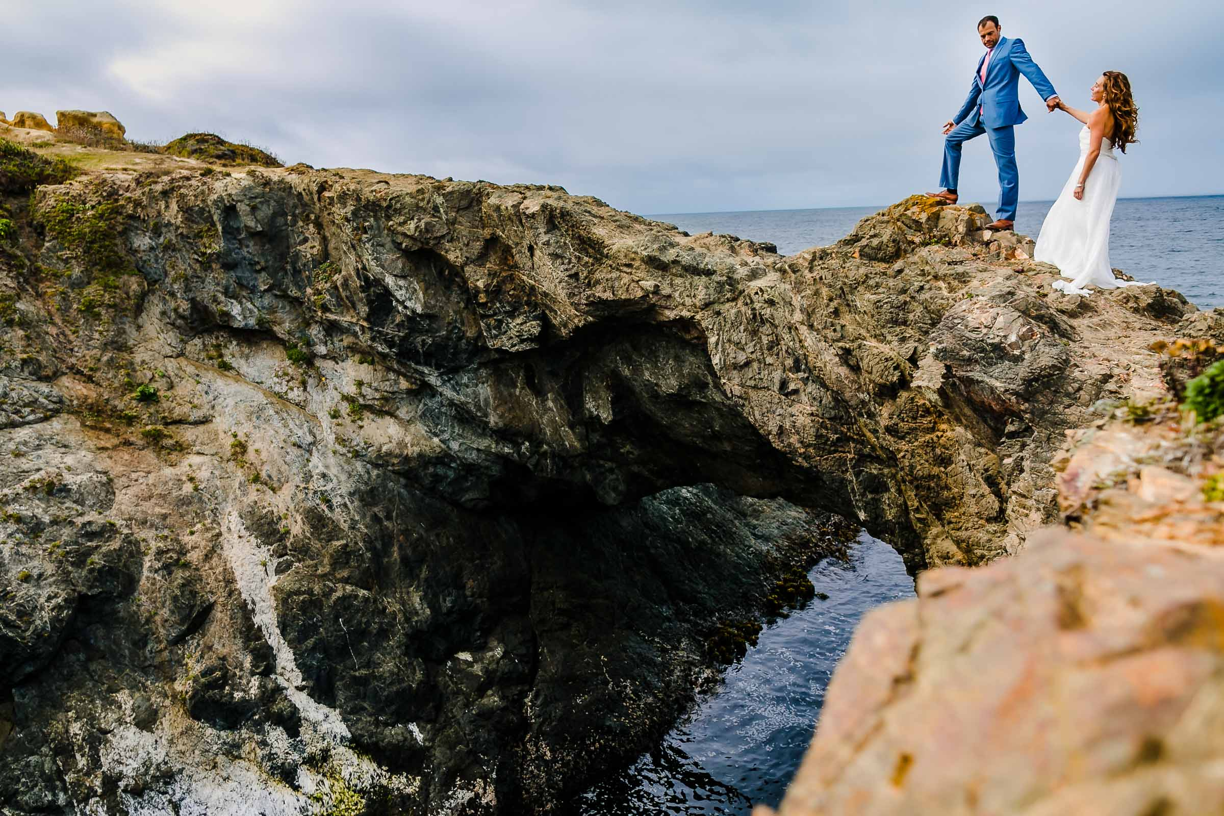 A photo of bride and groom walking along the cliffs together near the Pacific ocean the day after their Mendocino Coast wedding at Spring Ranch