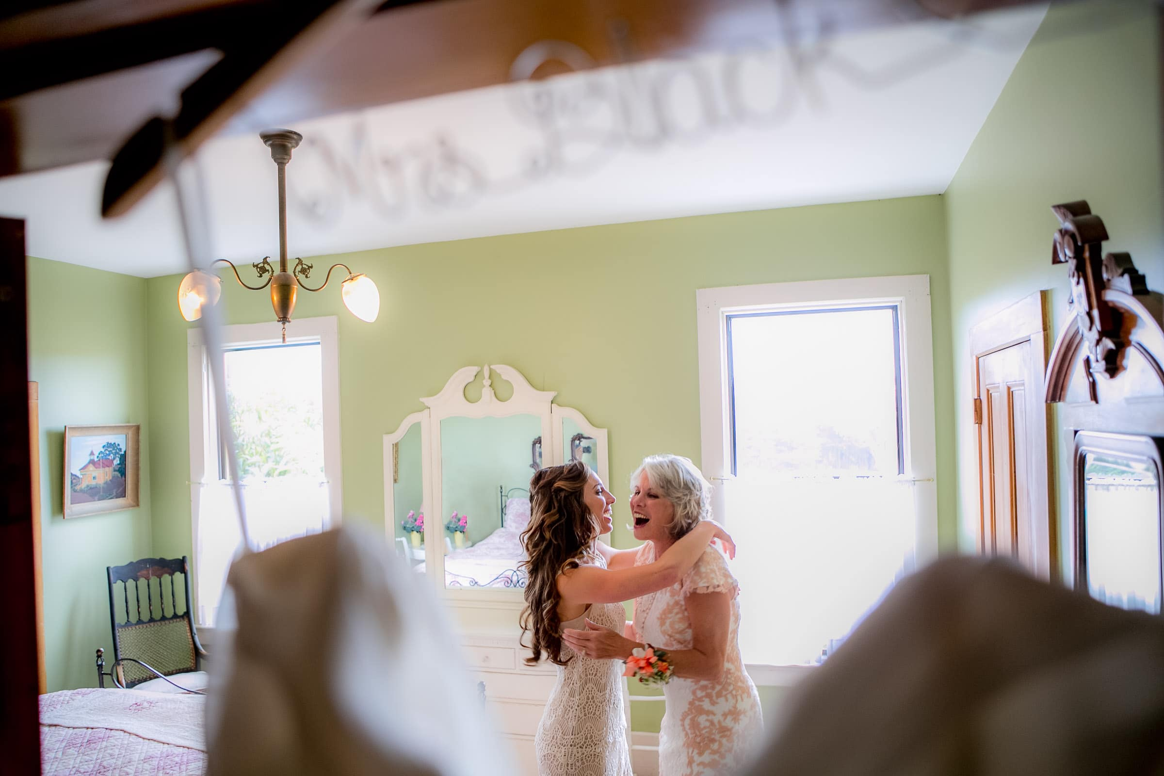 A bride and mother laughing and hugging while getting ready for a Mendocino Coast wedding at Spring Ranch