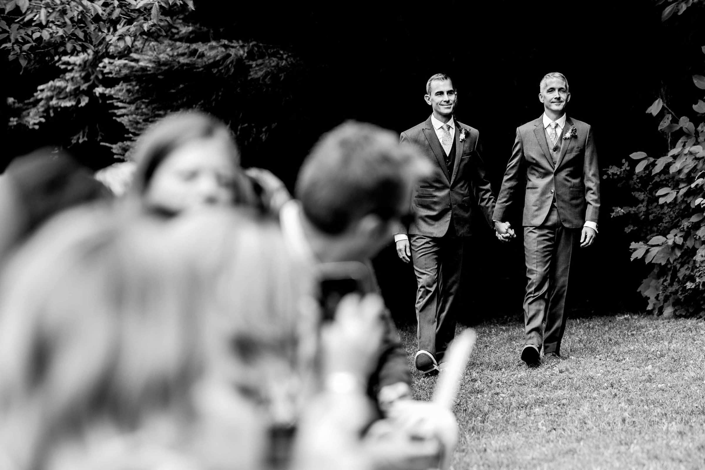 Two grooms walking hand and hand into their Mt Hood Organic Farms Wedding ceremony just outside Hood River, Oregon