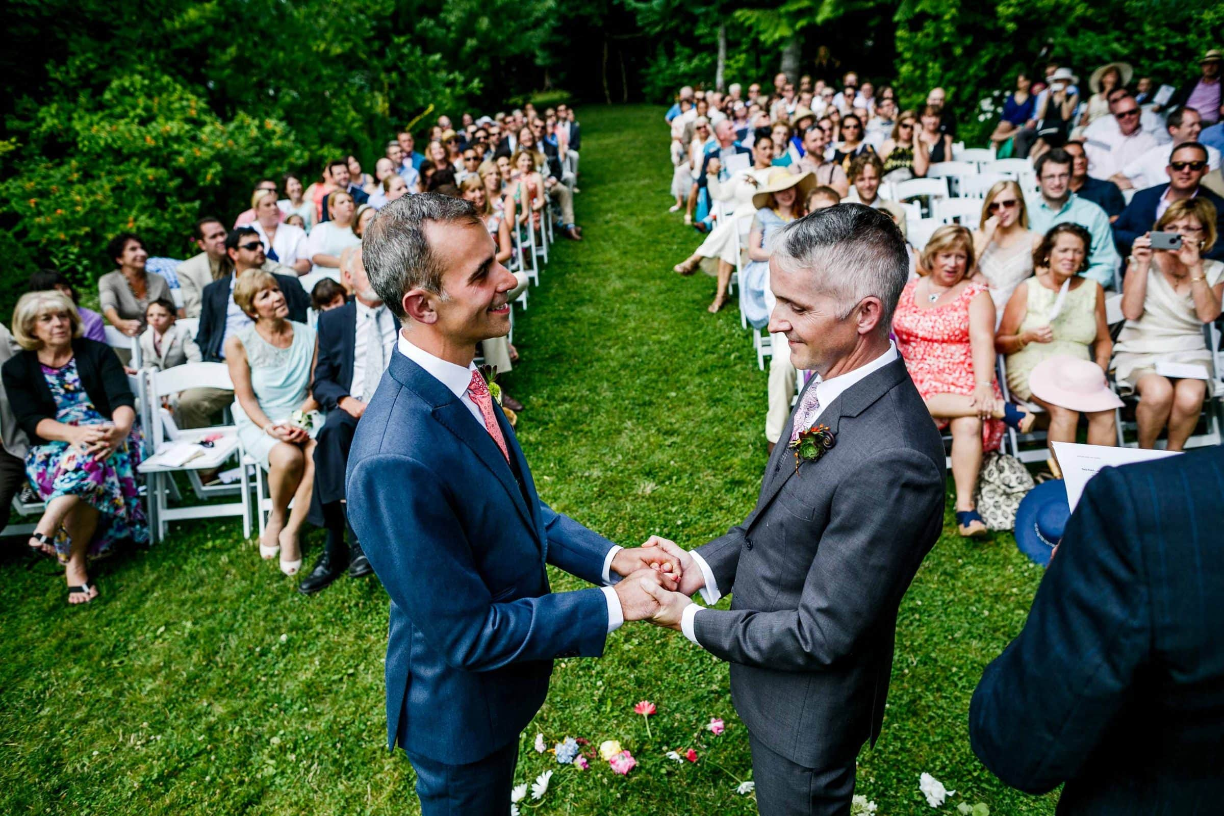 A wide angle view of two grooms holding hands with guests in the background during their Mt Hood Organic Farms Wedding ceremony just outside Hood River, Oregon