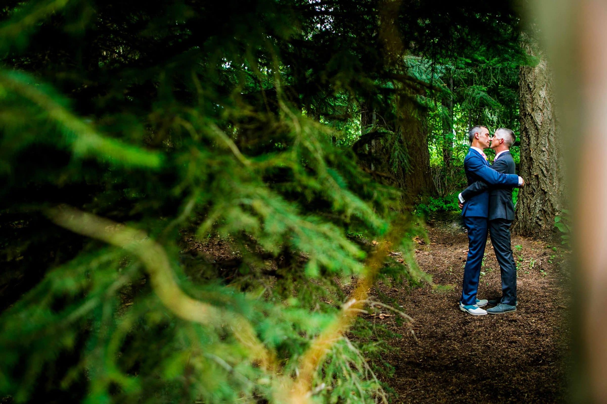 Two grooms embracing each other in the woods during their Mt Hood Organic Farms Wedding ceremony just outside Hood River, Oregon