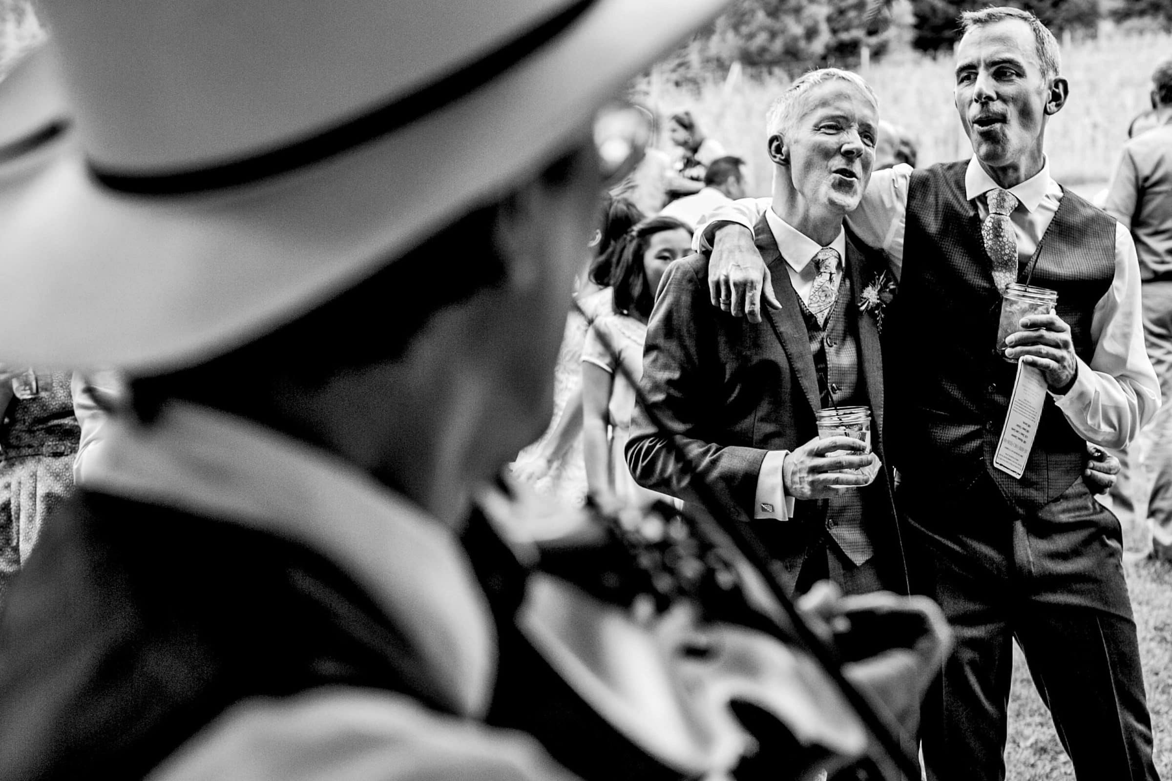 Two grooms singing together during their Mt Hood Organic Farms Wedding reception just outside Hood River, Oregon