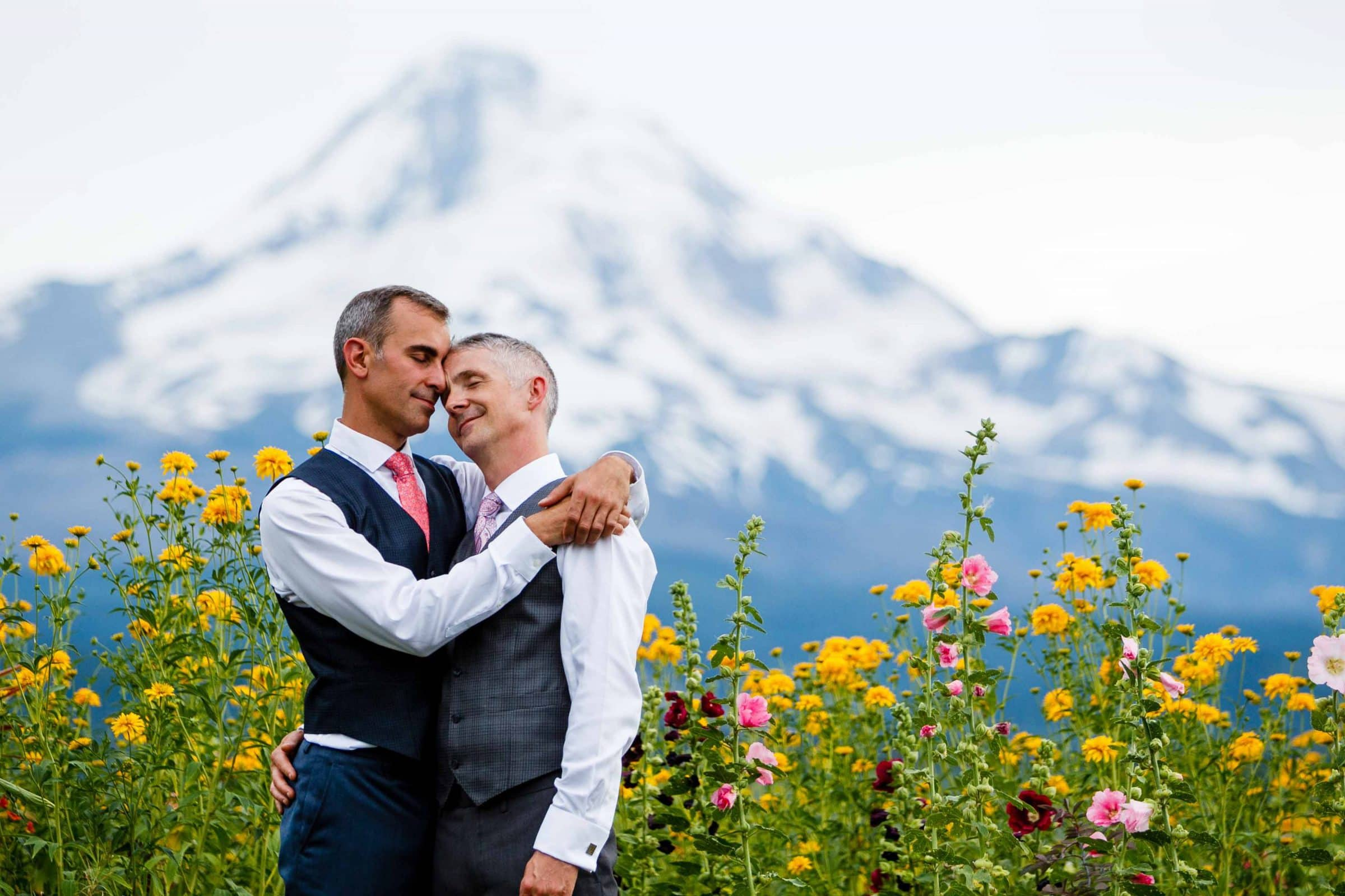 Two grooms holding each other with a mountain in the distance during their Mt Hood Organic Farms Wedding just outside Hood River, Oregon