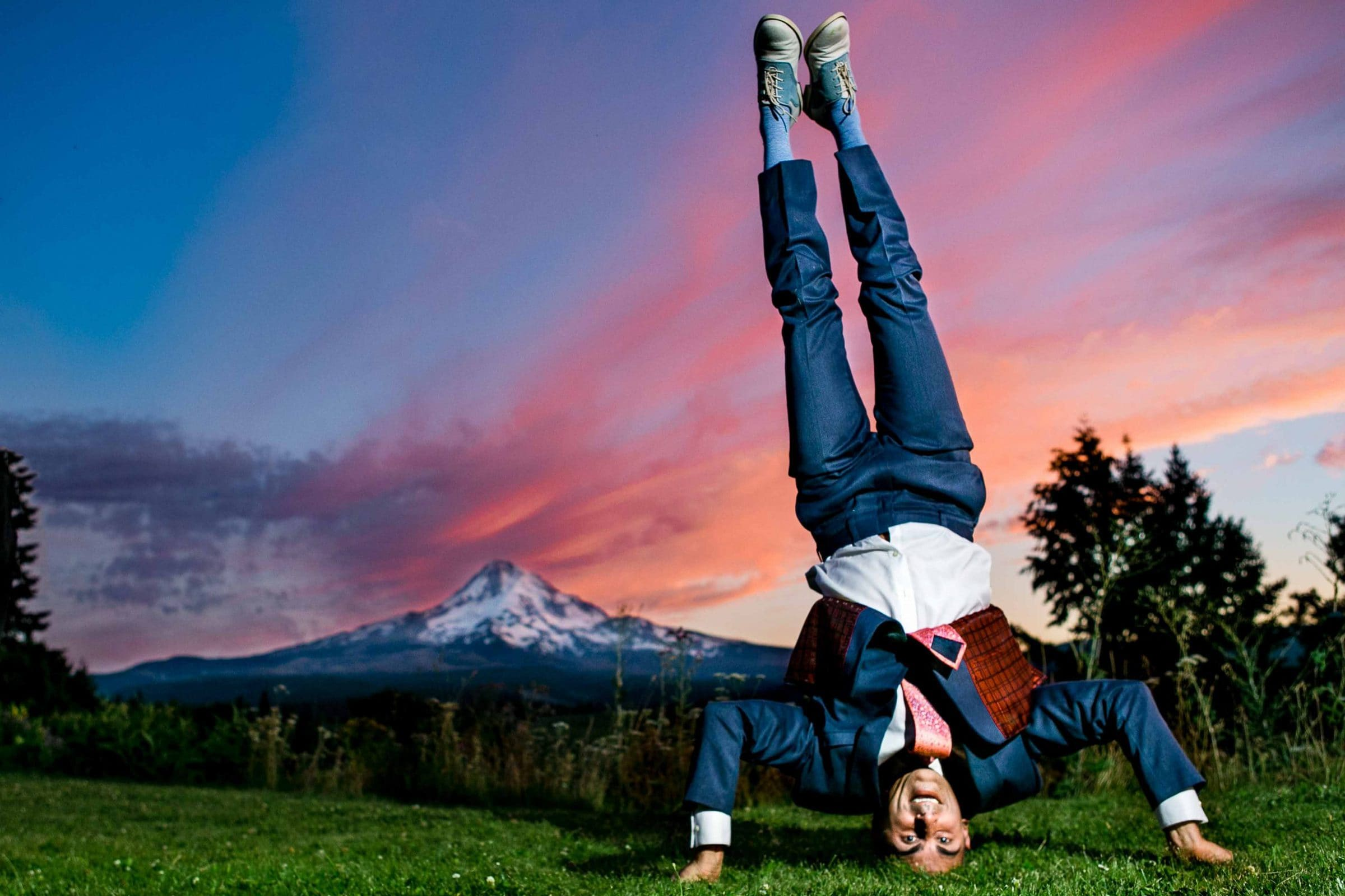 A comical photo of a groom standing on his head during a Mt Hood Organic Farms Wedding reception just outside Hood River, Oregon