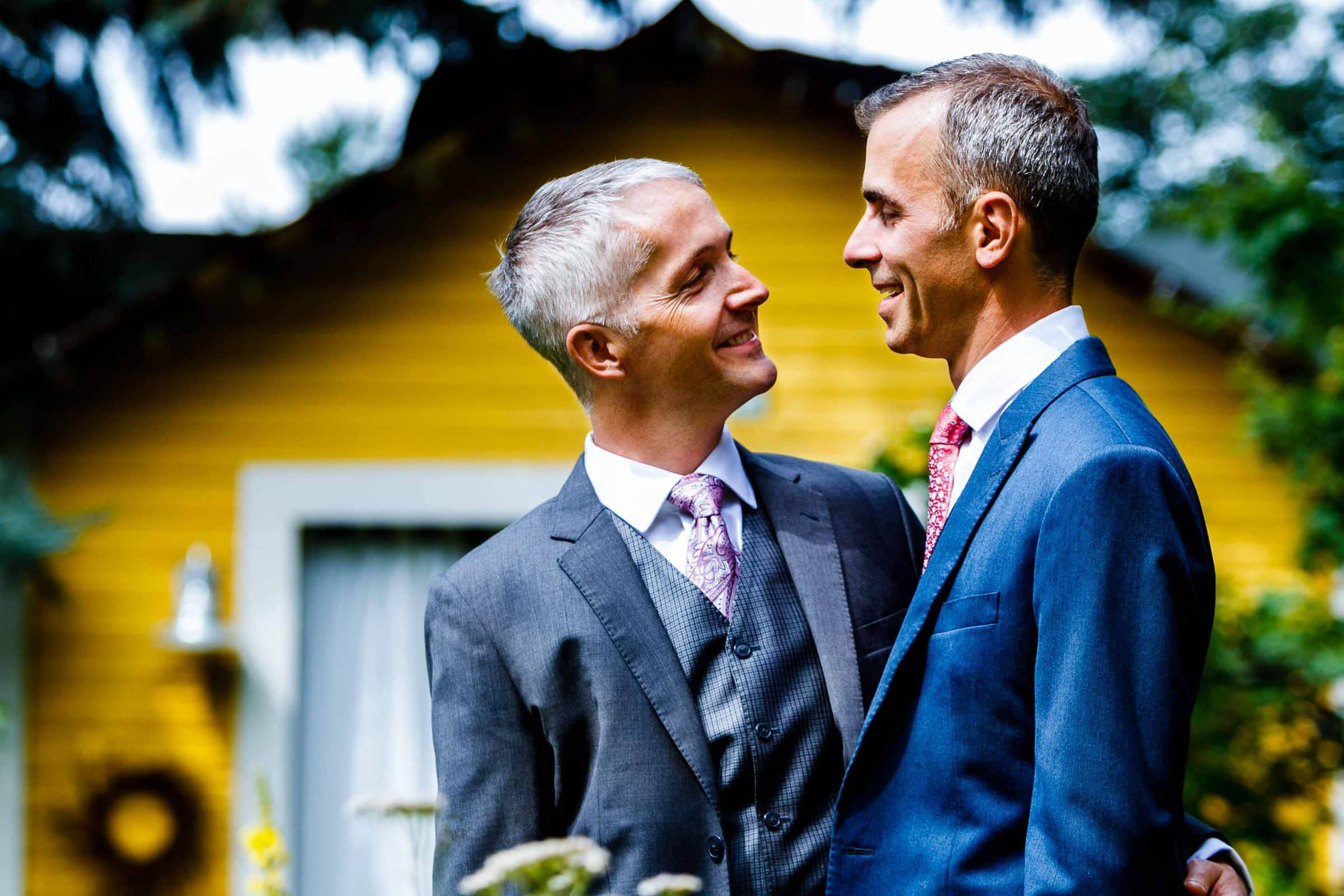 Two grooms enjoying a moment together before their Mt Hood Organic Farms Wedding ceremony