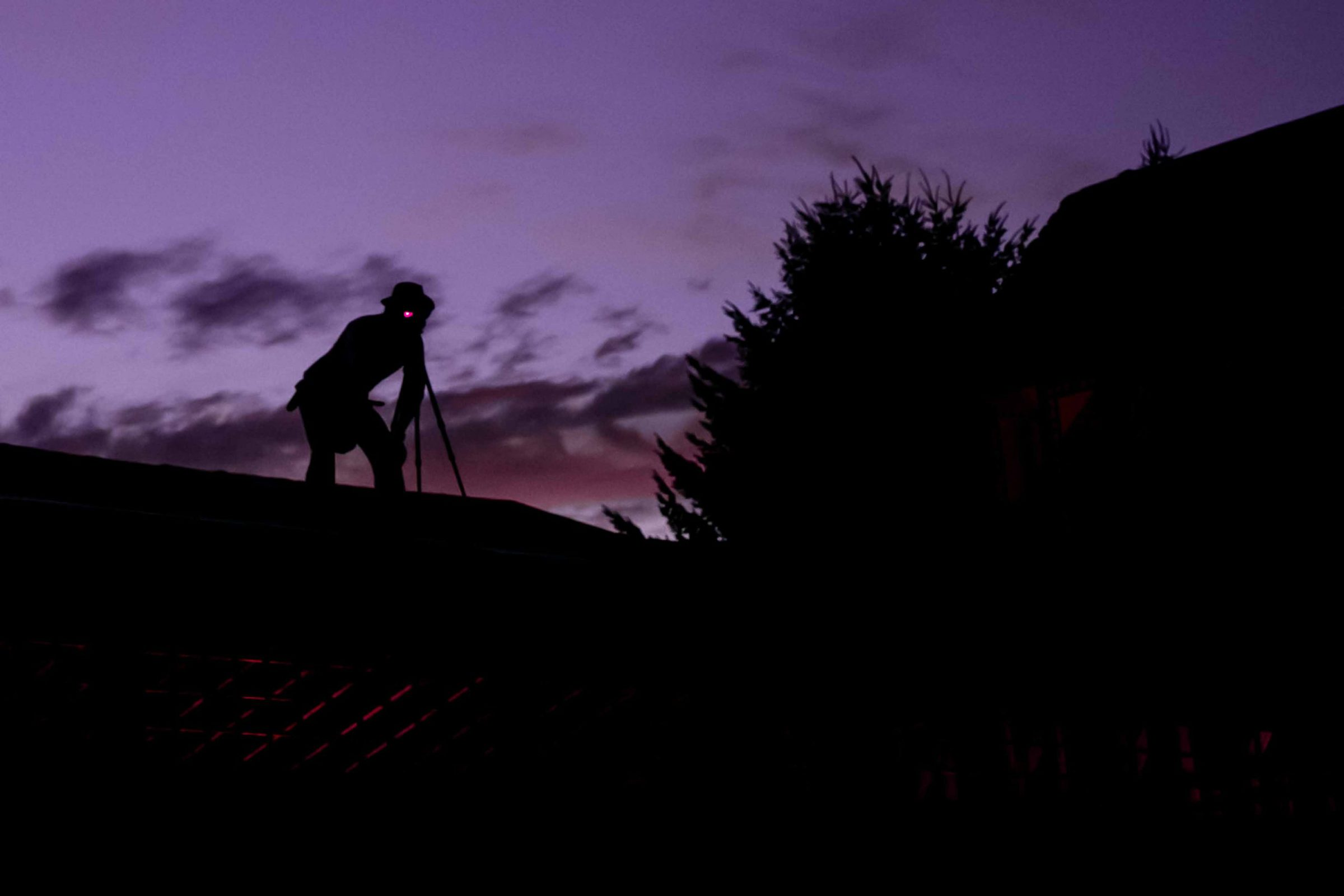 An award winning wedding photographer shooting a photo from the rooftop at during a Mt Hood Organic Farms Wedding reception just outside Hood River, Oregon