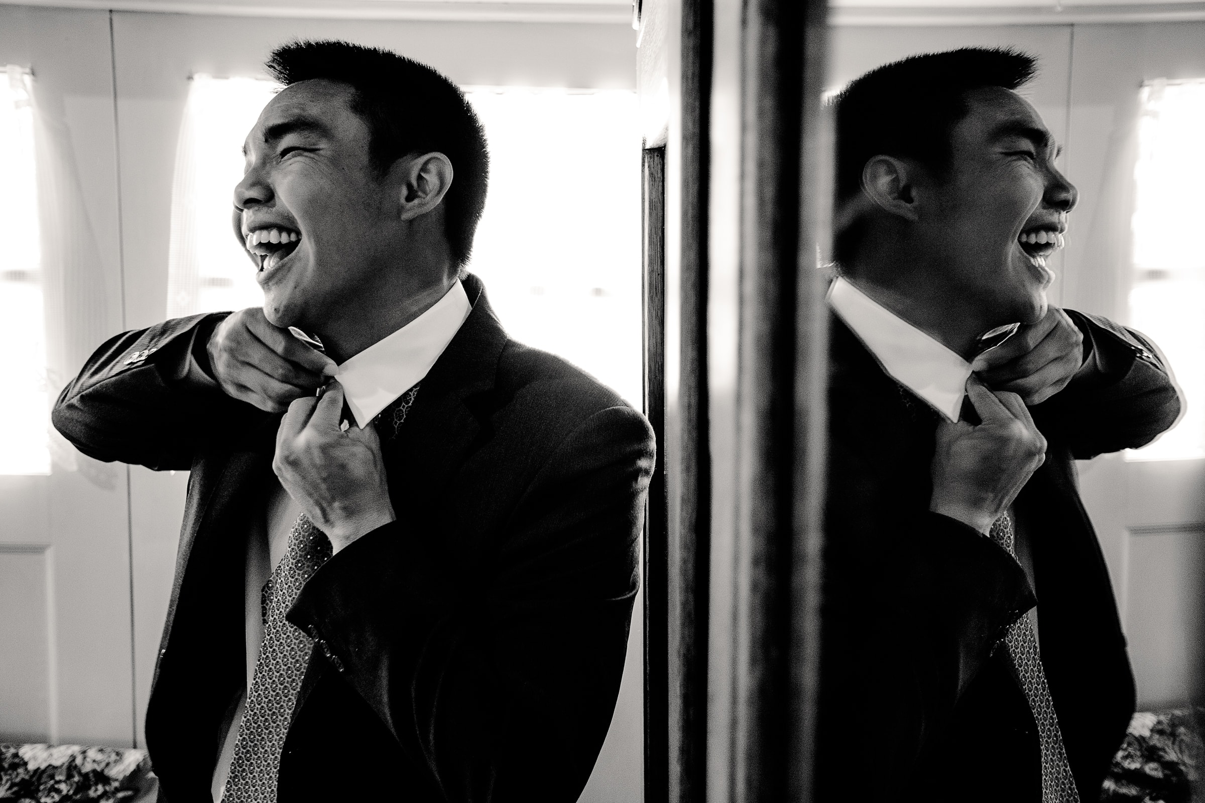 Groom putting on his tie while laughing before his Mt Hood Organic Farms Wedding ceremony