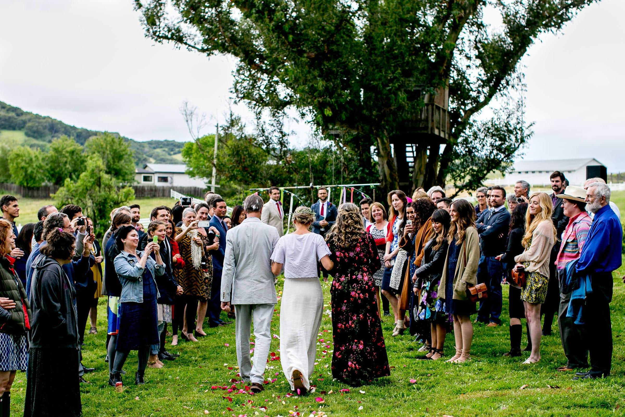 Wide angle view of bride and groom walk into their Sonoma wine country wedding ceremony