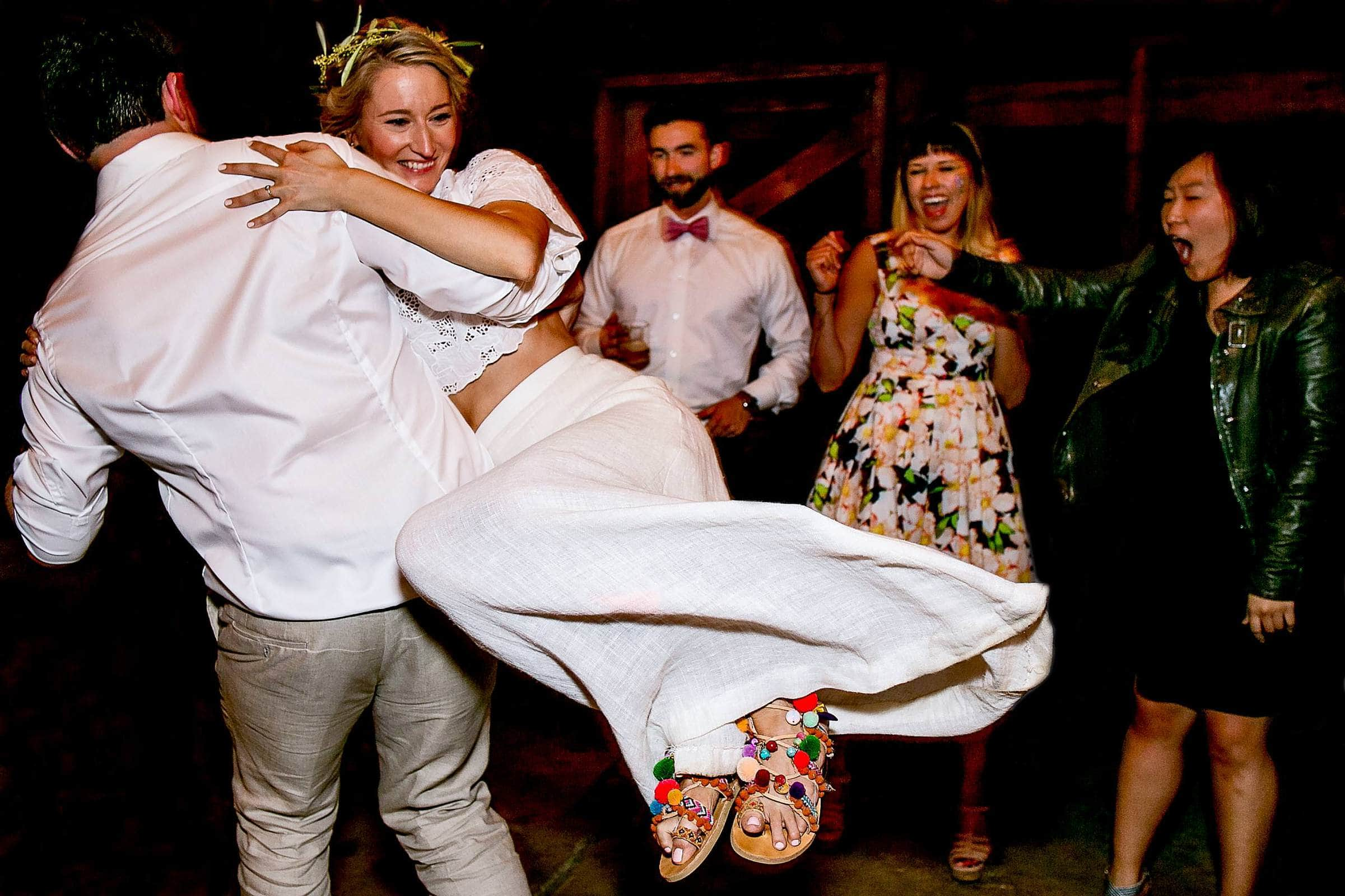 Groom and bride dancing and spinning during their Grateful Dead barn during a Sonoma wine country wedding reception