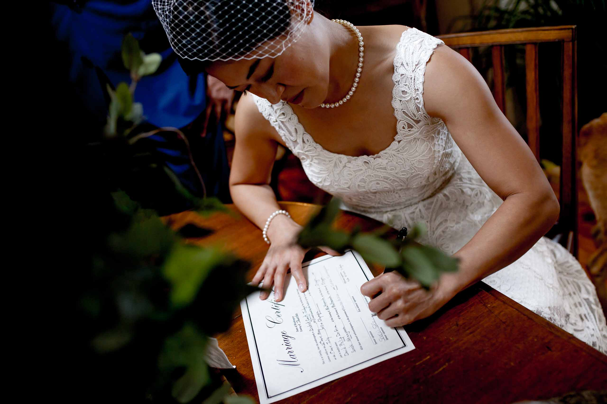 Bride signing a wedding certificate during a private Seattle elopement ceremony