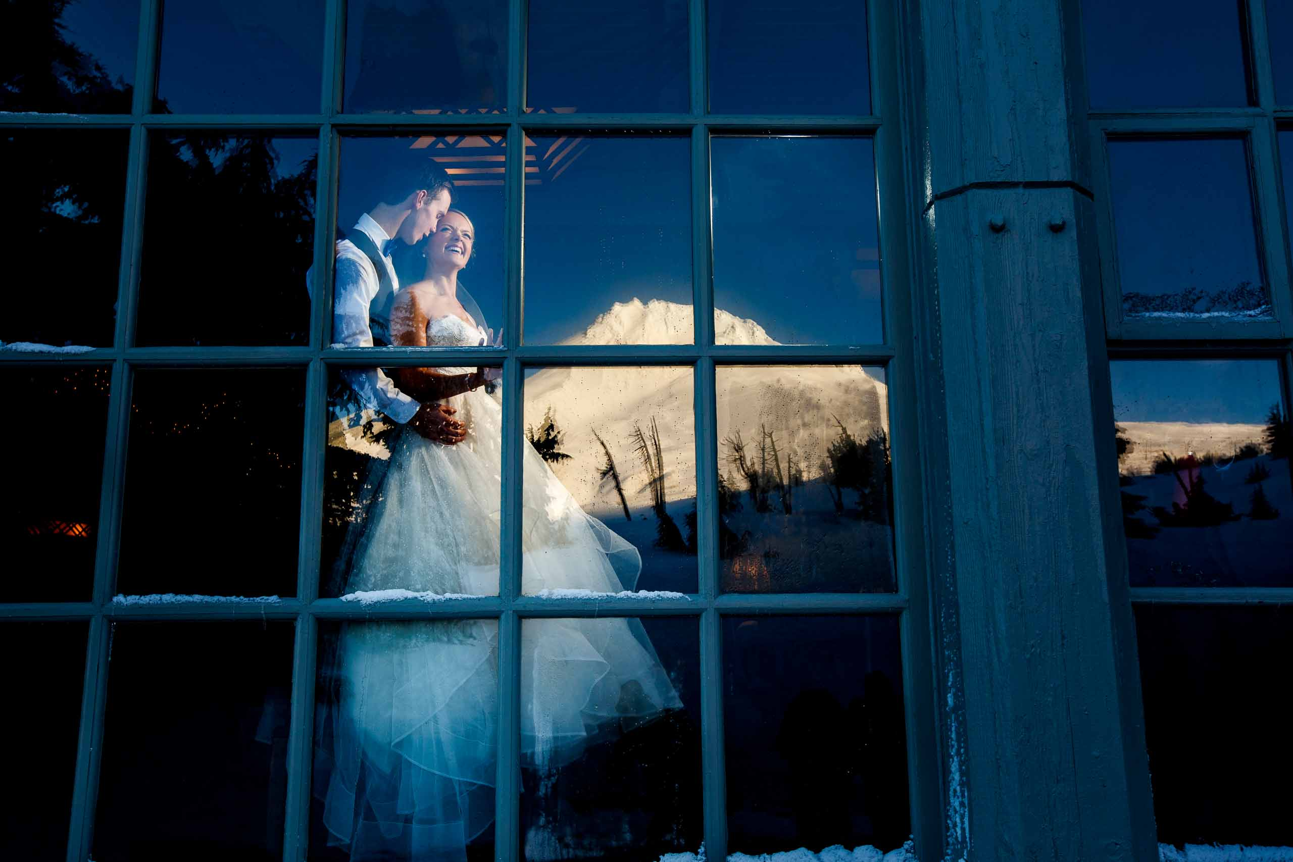 Bride and groom portrait with Mt Hood reflecting in the window at Timberline Lodge moments before their Silcox Hut wedding