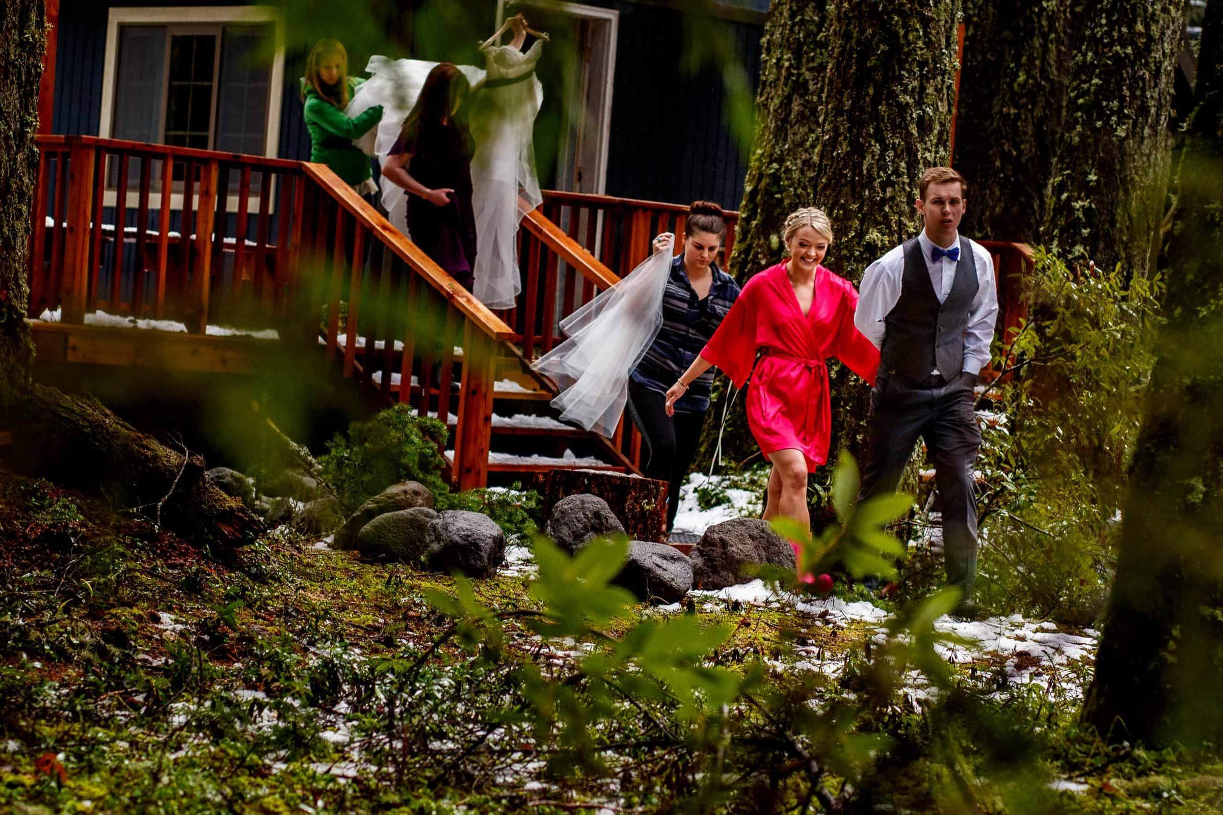 Bride and groom walking to get dress on in the woods for their Silcox Hut wedding