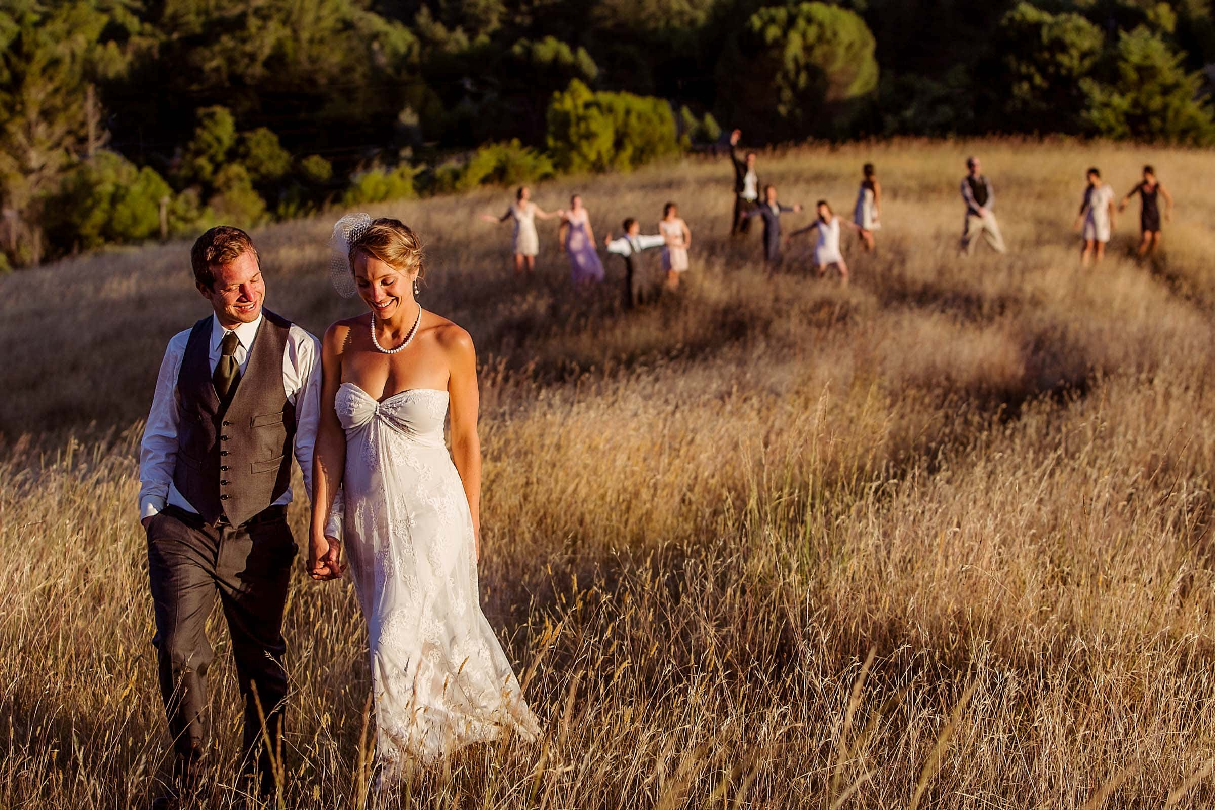bride and groom walking at sunset in gorgeous light with bridal party behind them laughing