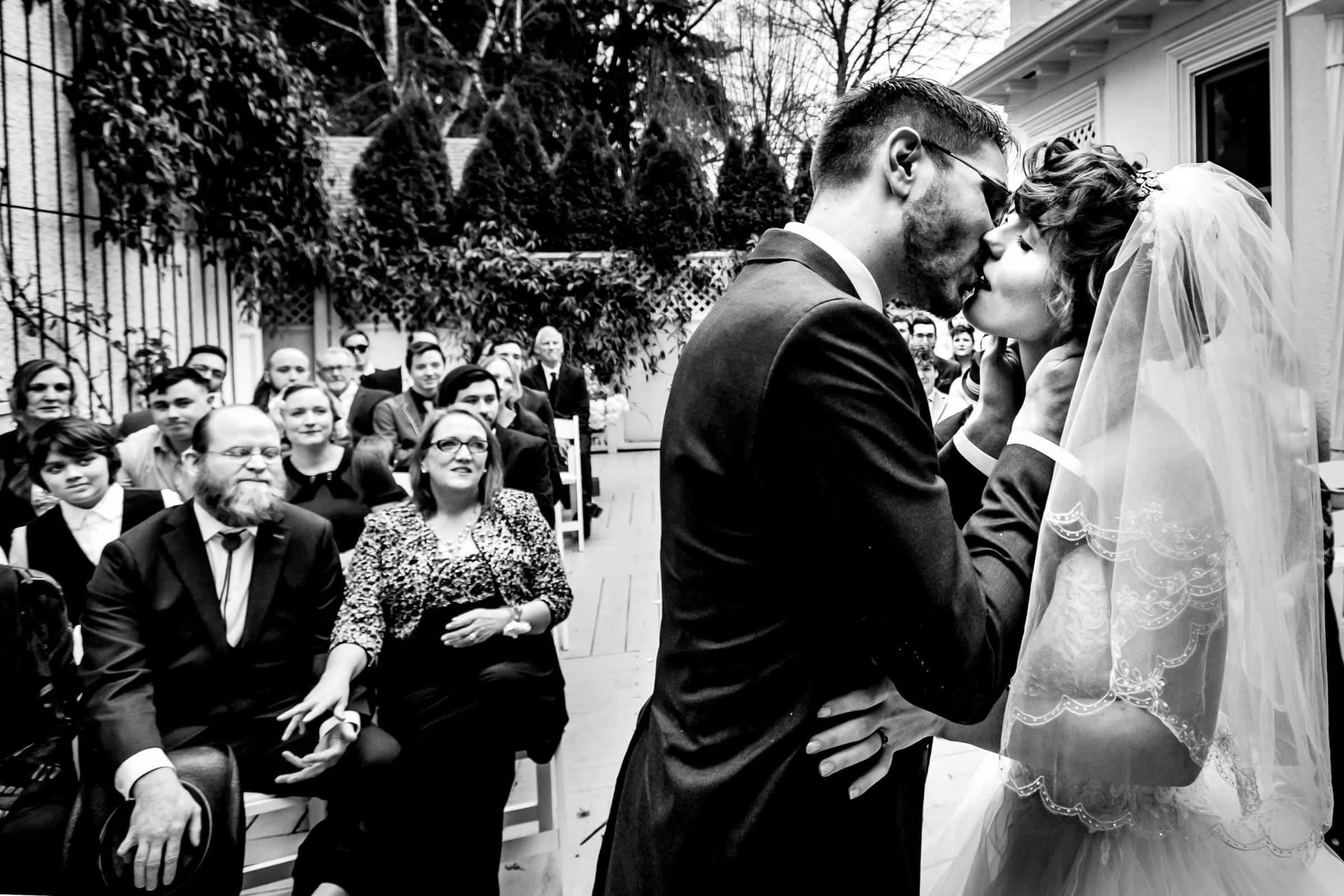 Bride and groom kissing each other during their Portland White House wedding ceremony