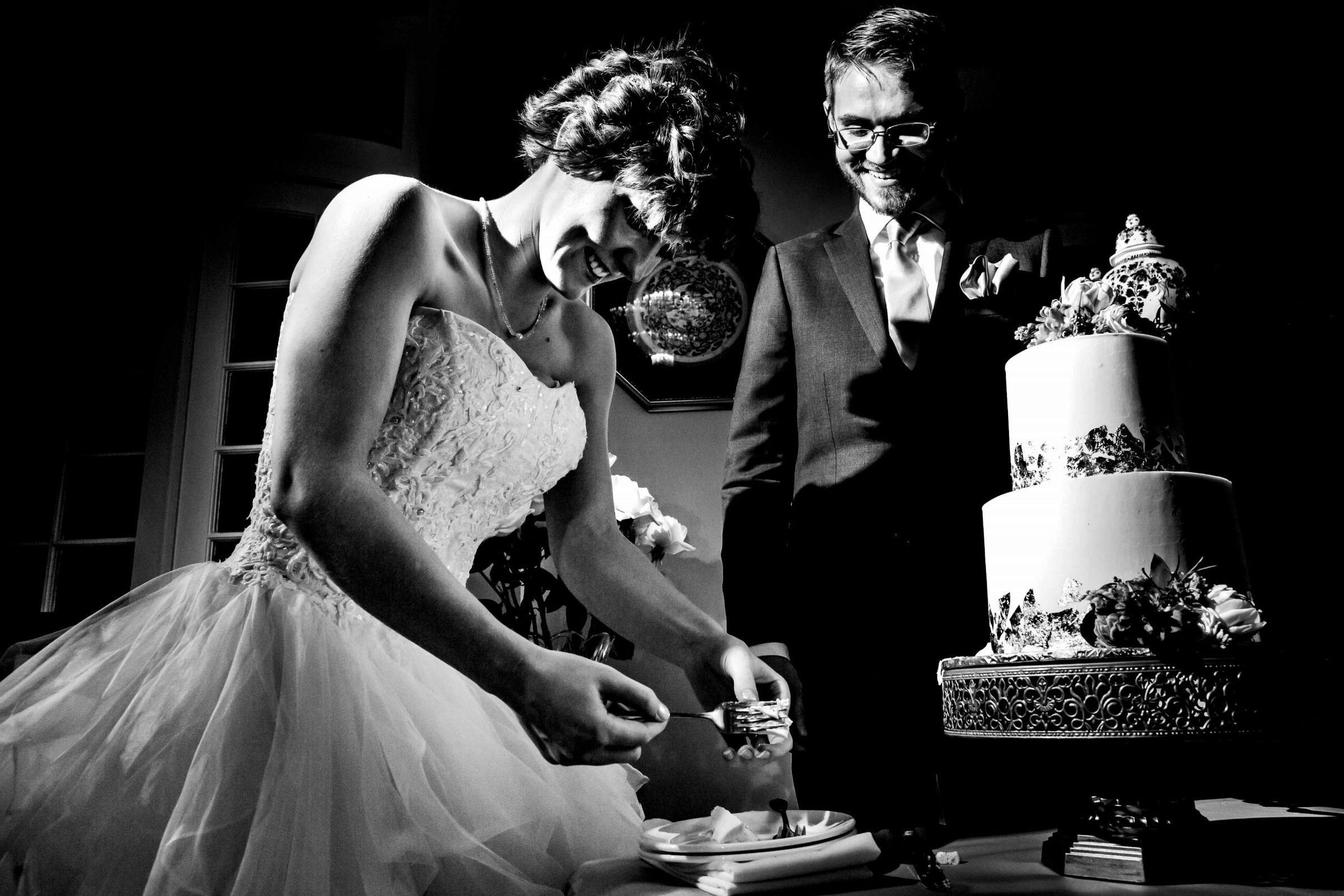 Bride and groom cutting cake during their Portland White House wedding ceremony