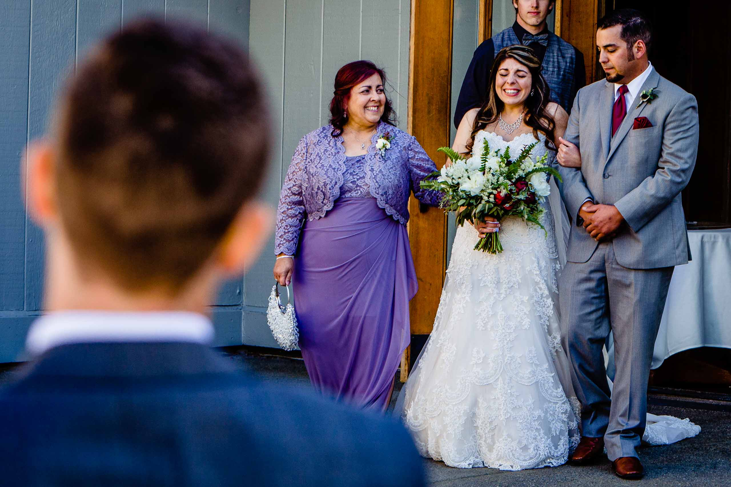 Emotional bride with her mother and brother while walking into her Timberline Lodge Wedding ceremony