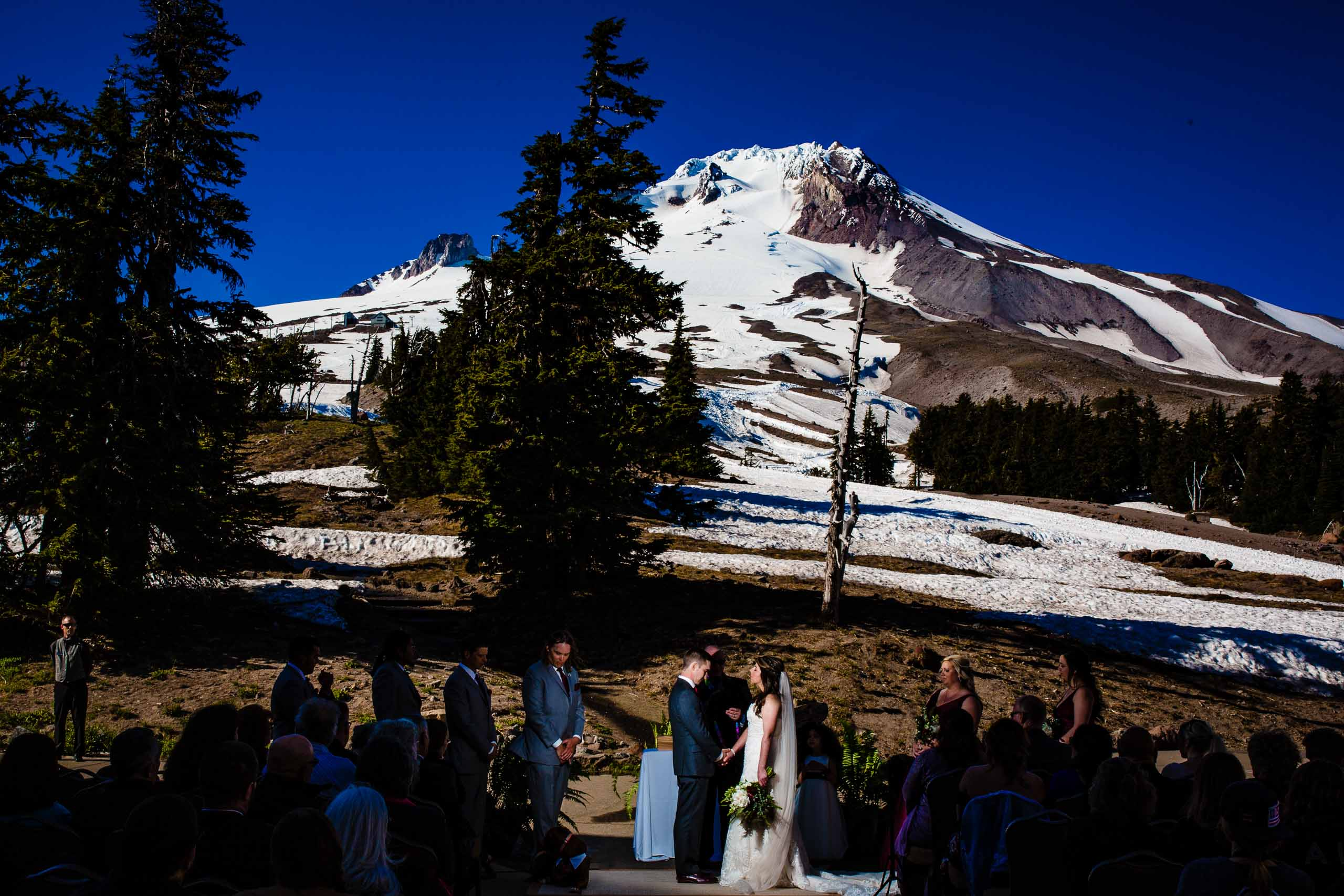Wide angle perspective of Mt Hood with a bride and groom and guests during their Timberline Lodge Wedding ceremony