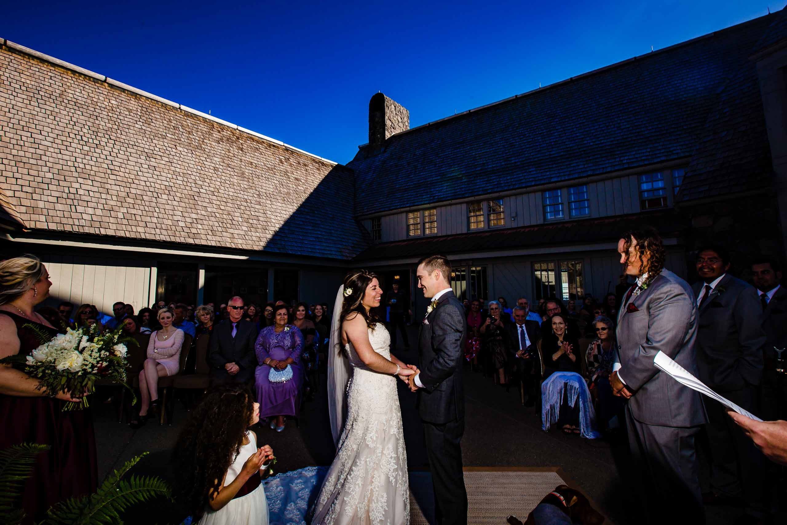 Bride and groom beautifully lit up during their Timberline Lodge Wedding on the patio outside in the sun